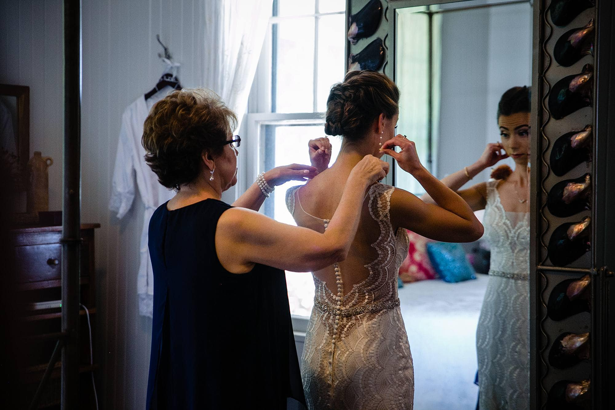 mom helping daughter with wedding dress
