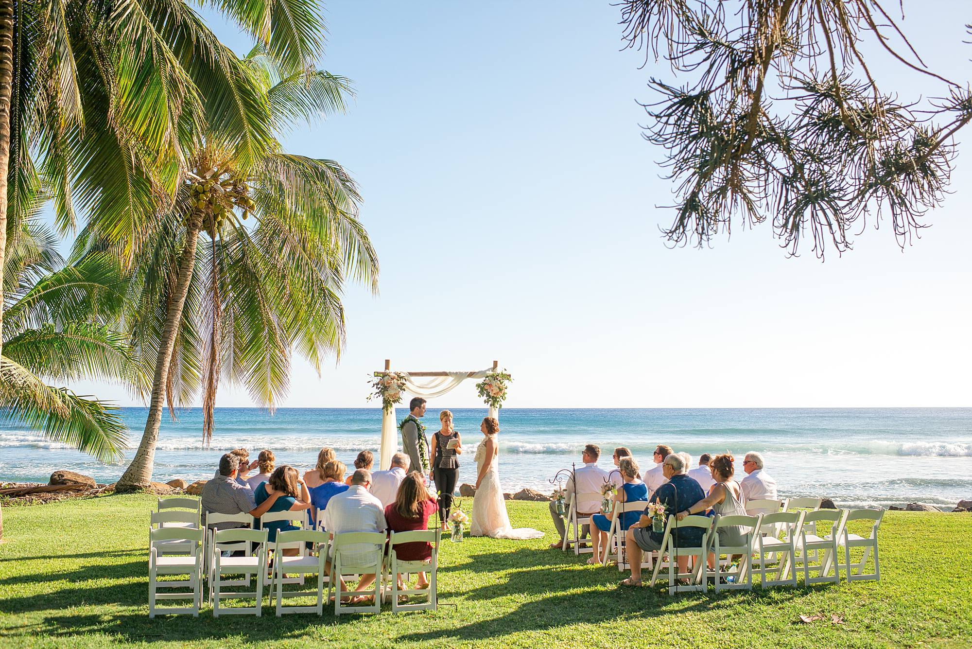 wedding guests in white chairs and couple getting married overlooking the pacific