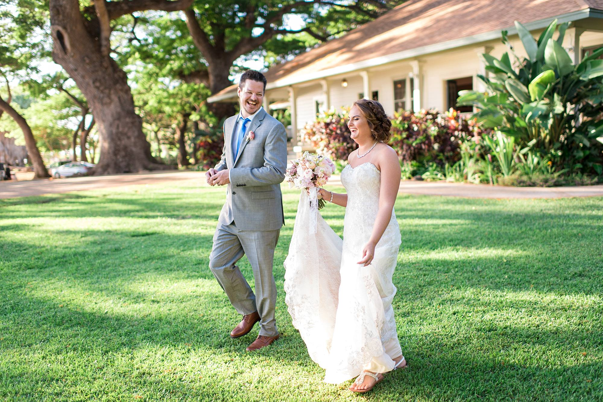 couple walking on grass with Olowalu Plantation house int he background
