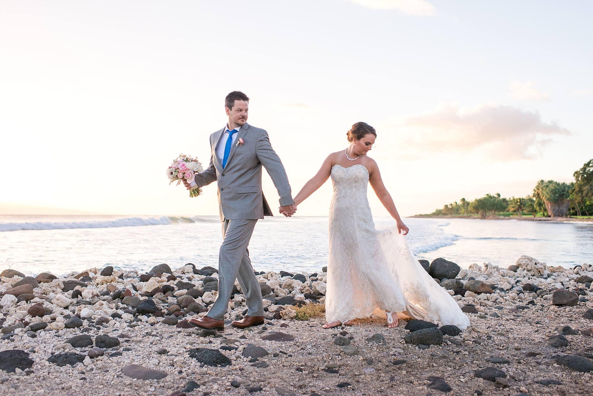 married walking on beach rocks