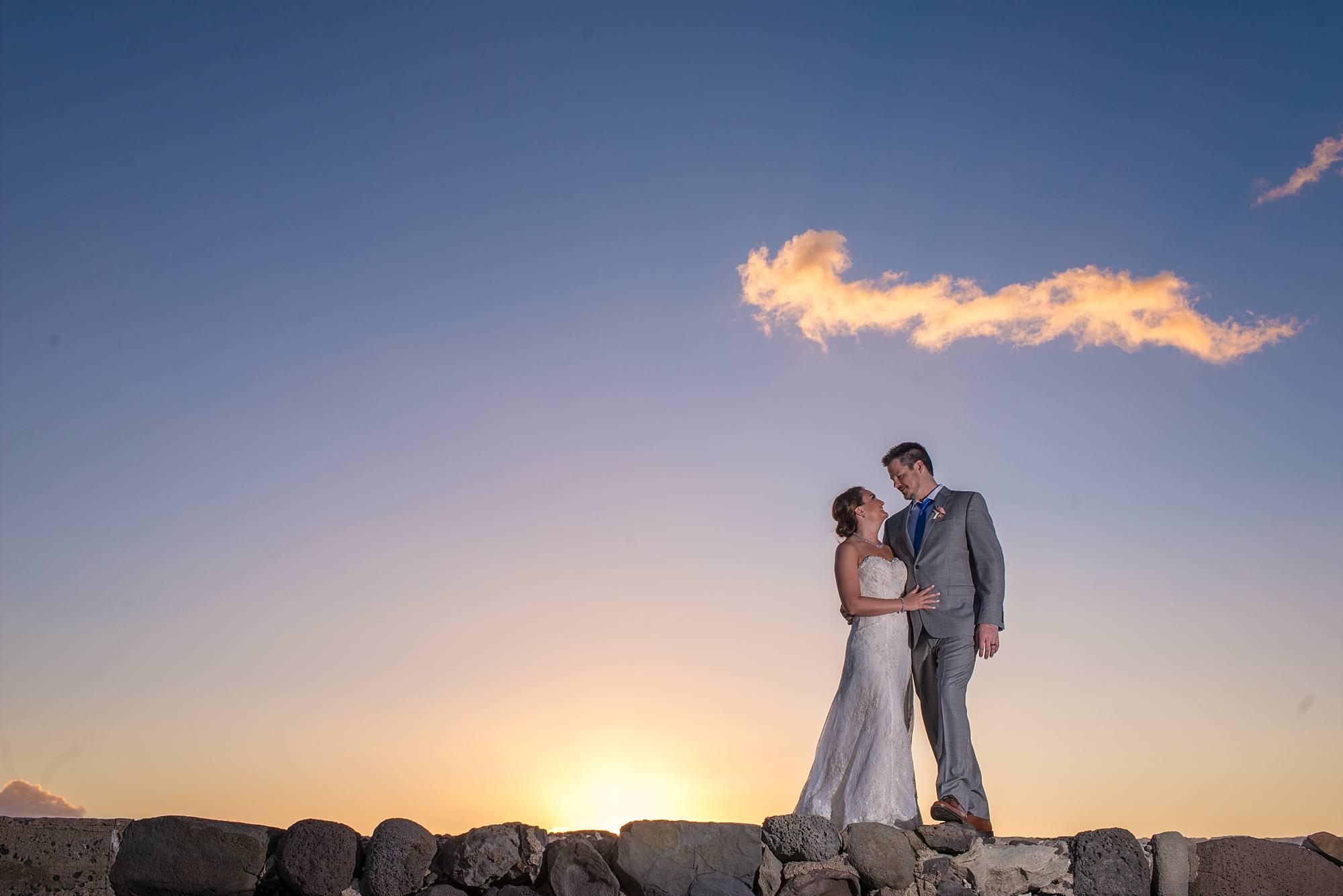 bride and groom on top of rocks