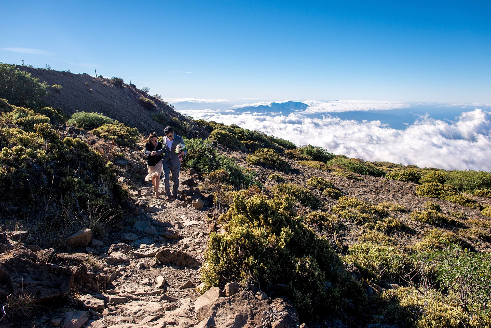 couple walking up rocky path on mountain