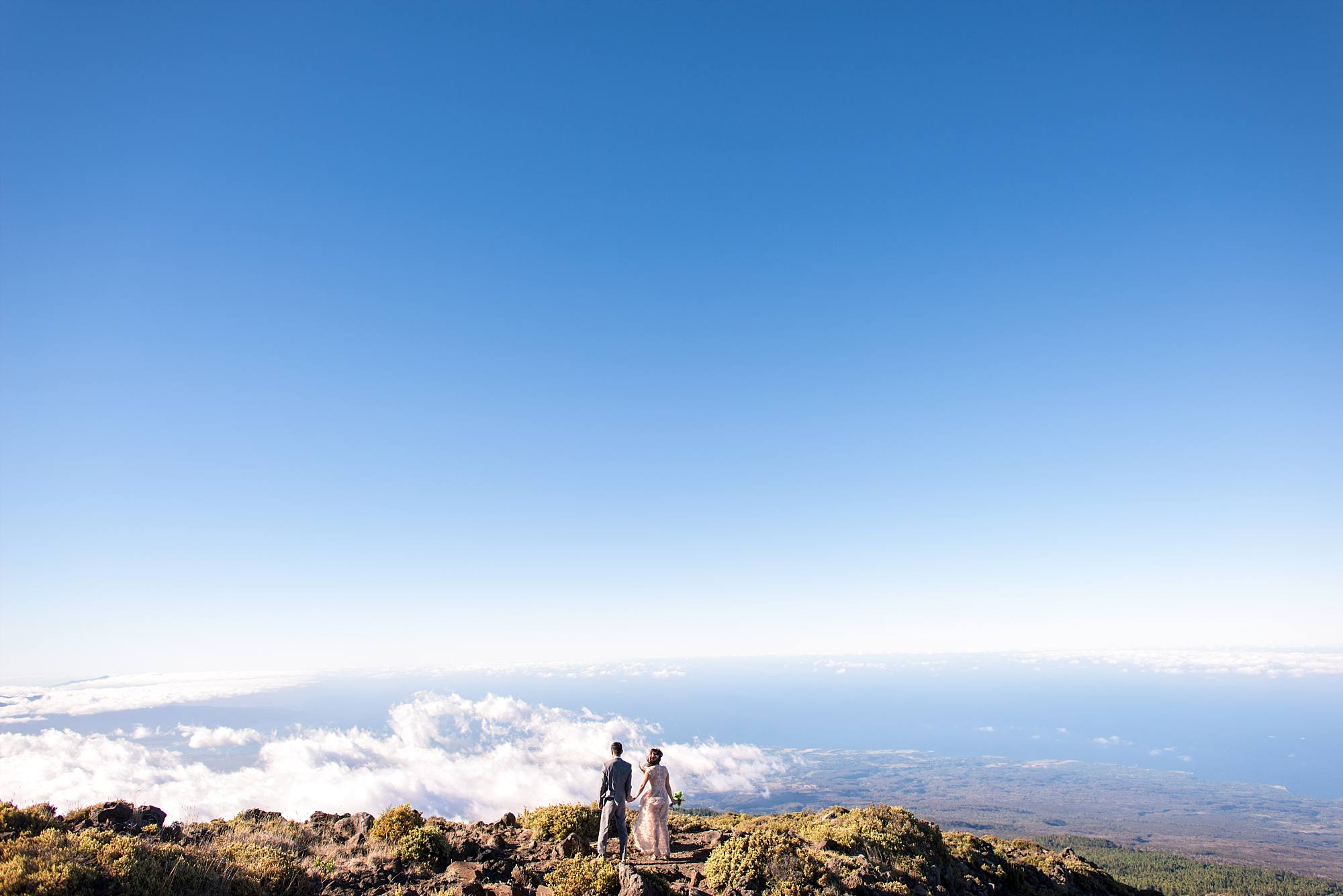 bride and groom above the clouds on side of mountain