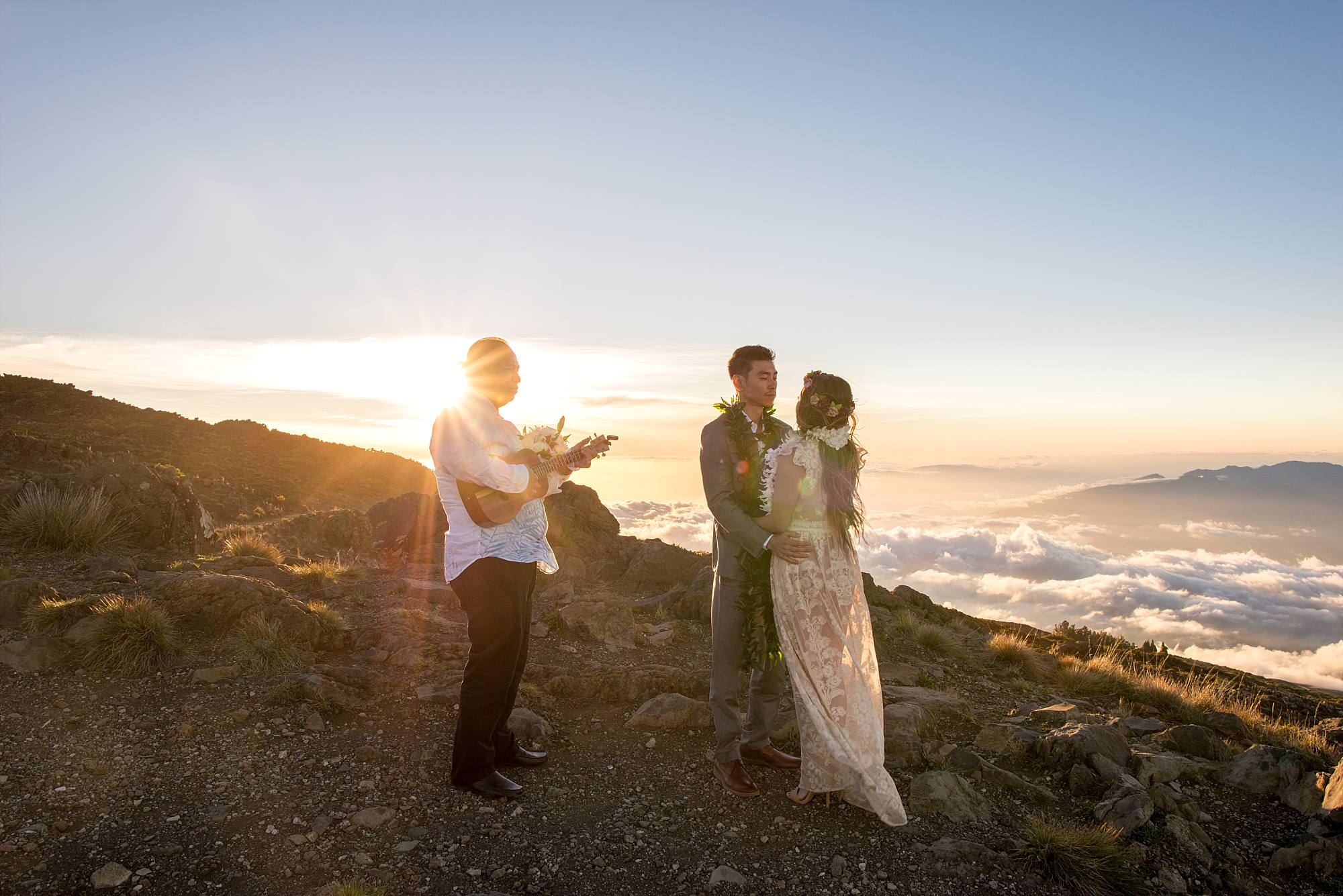 wedding officiant laying ukulele while bride and groom hold on to one another
