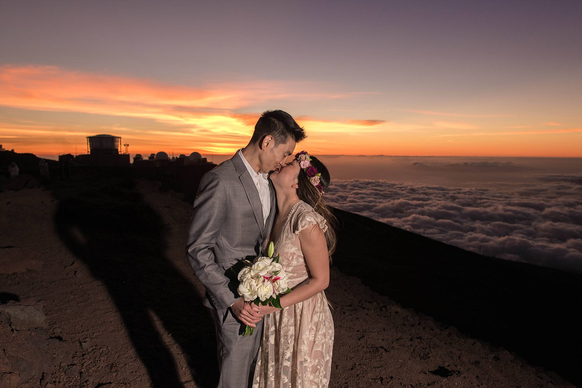 husband and wife kissing at sunset above clouds