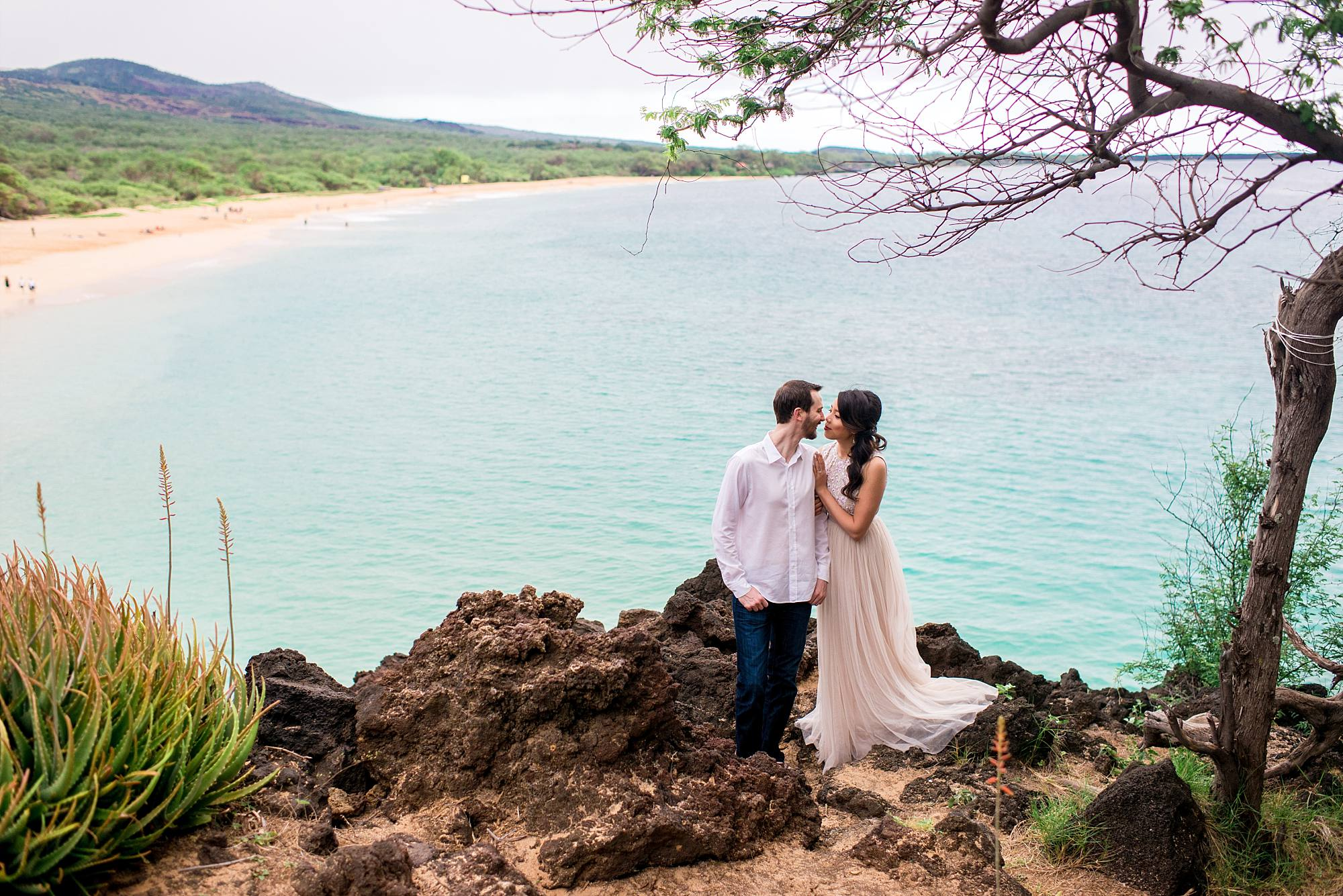 lovers standing atop lava rock cliff with ocean behind them