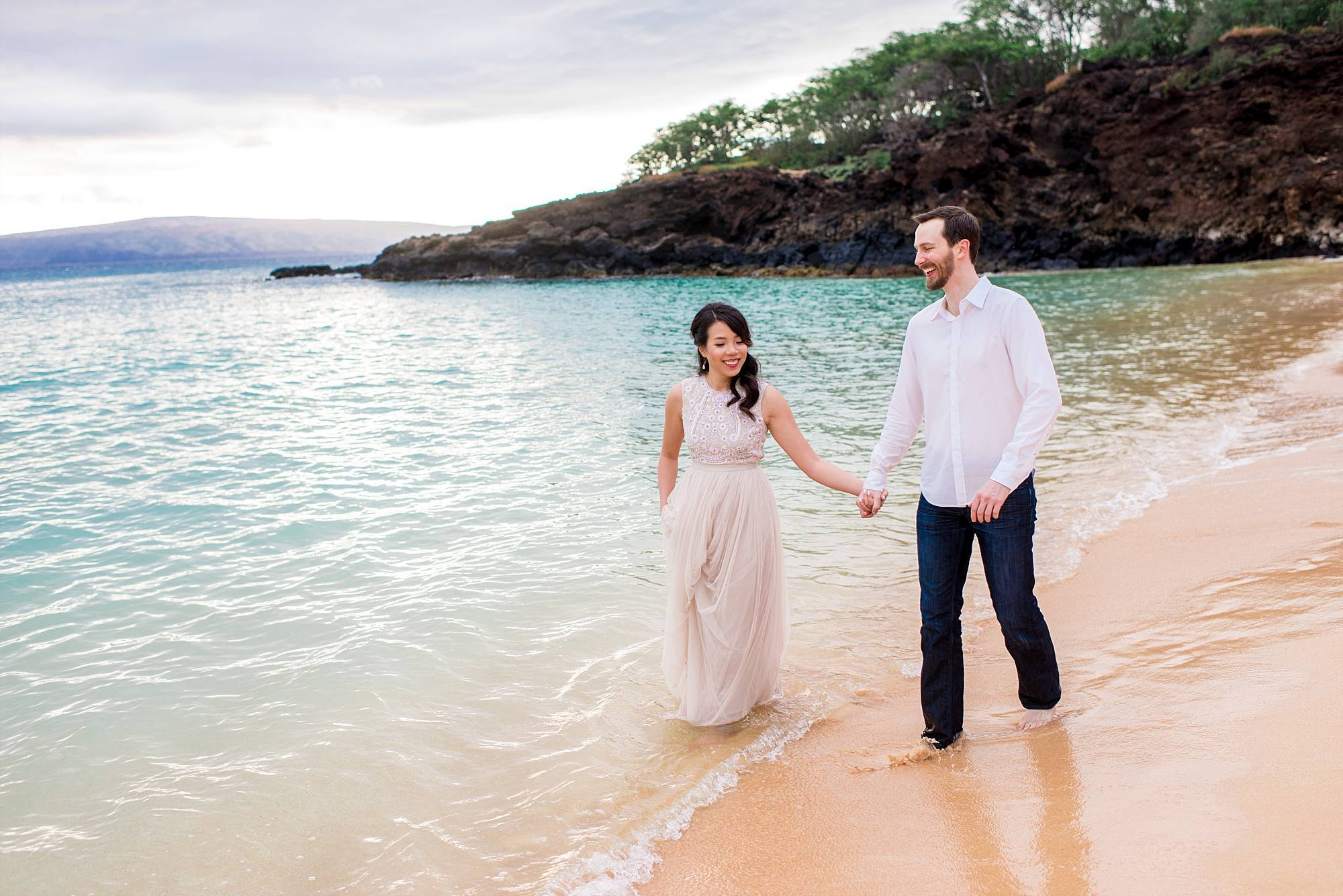 couple walking towards camera holding hands with turquoise water behind them