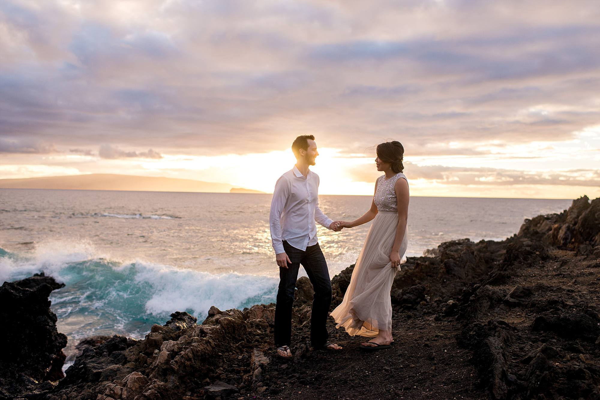 couple on lava cliff holding hands