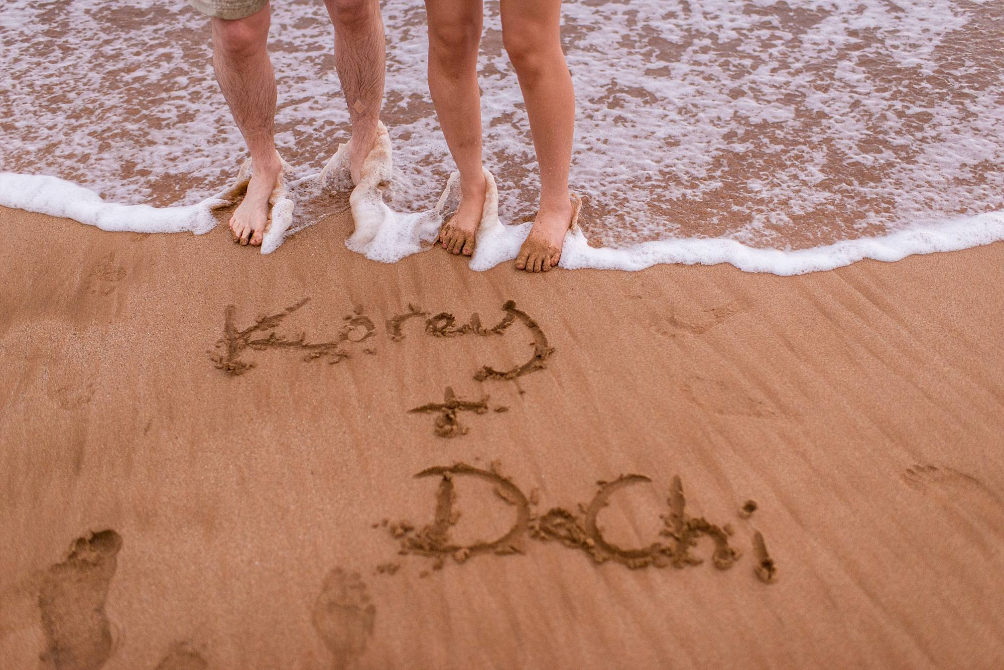 Lovers names written in the sand by their feet