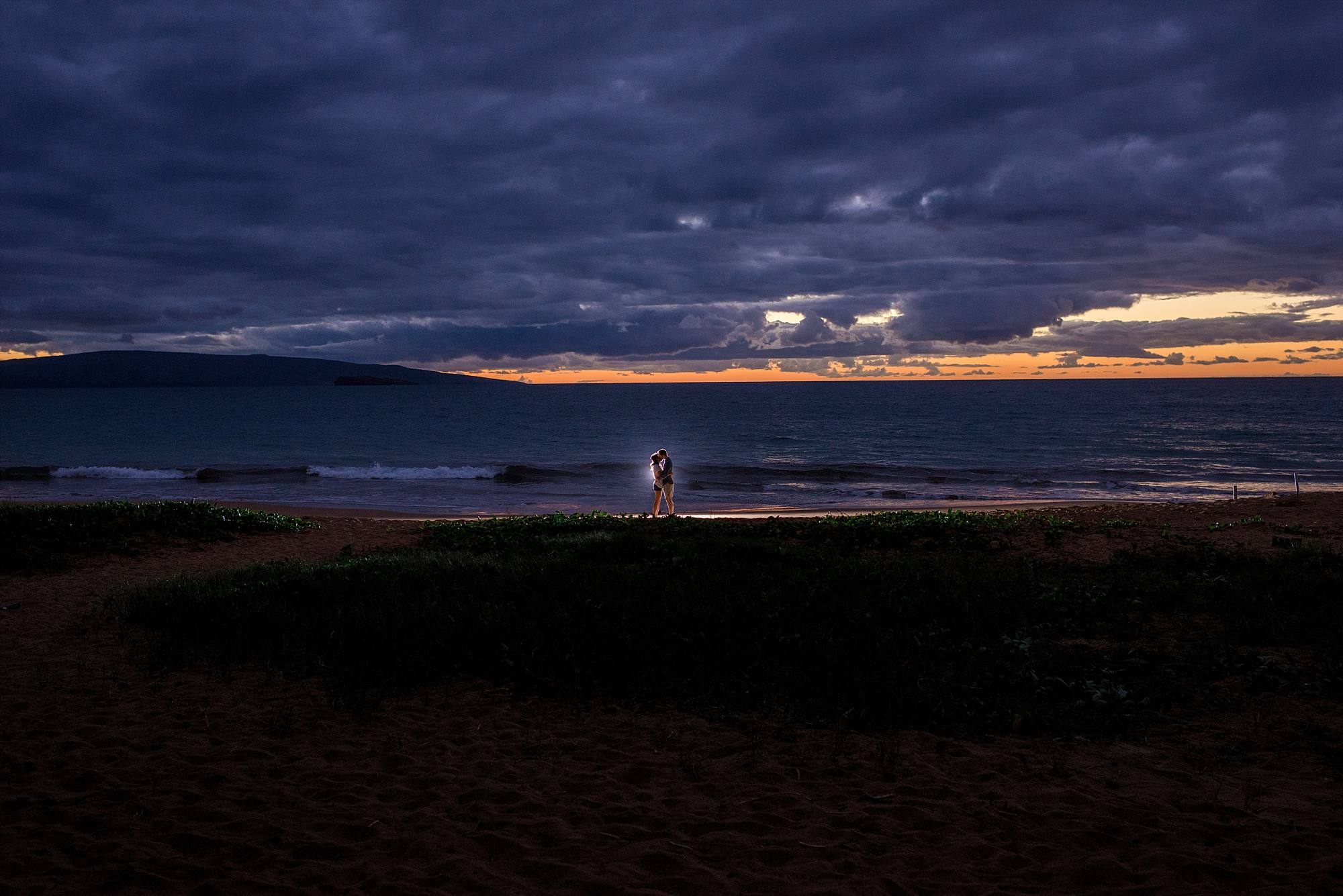 couple kissing on Maui beach, sunlight fading into the water