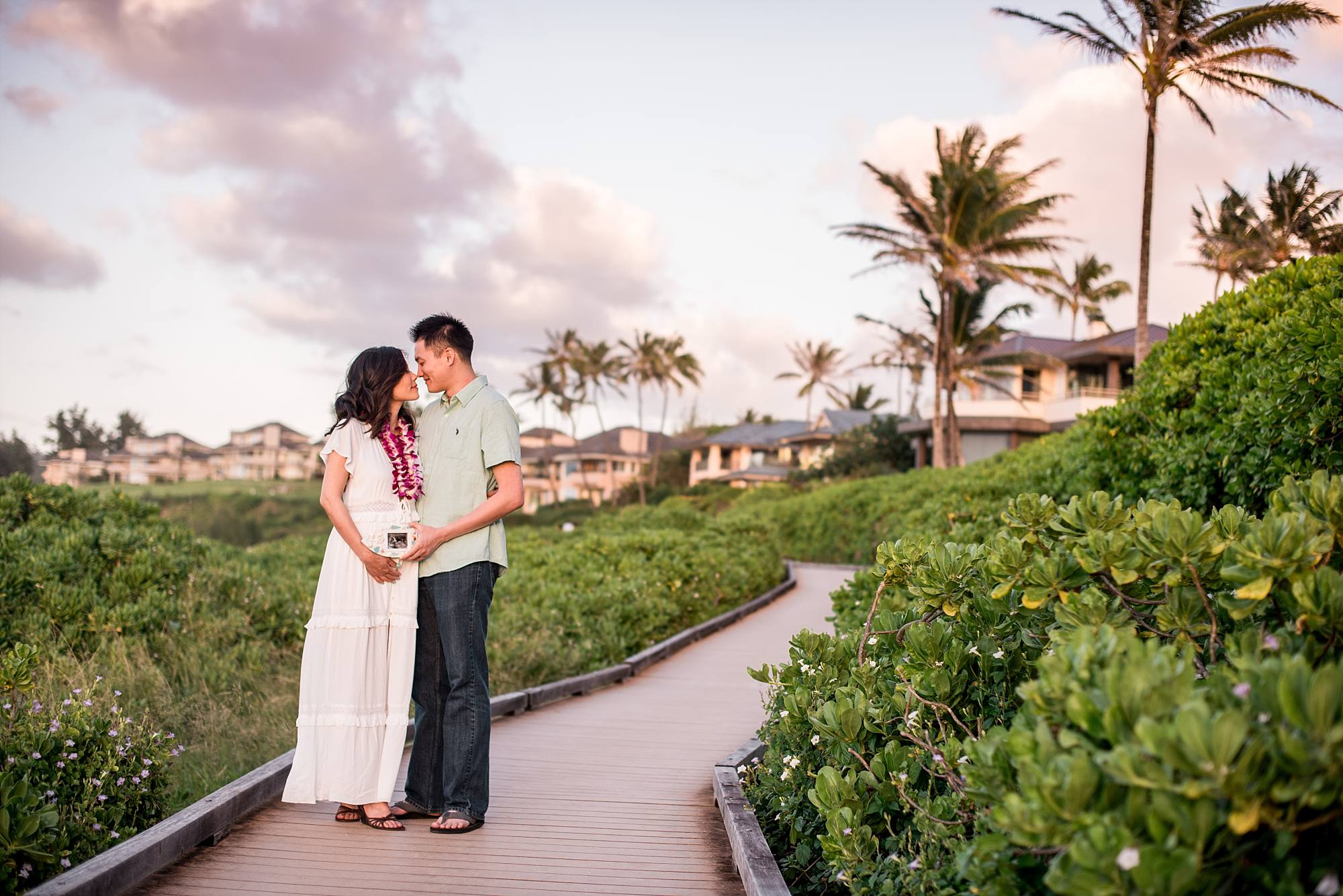 couples maternity shot on Maui boardwalk with ultrasound in front of her stomach