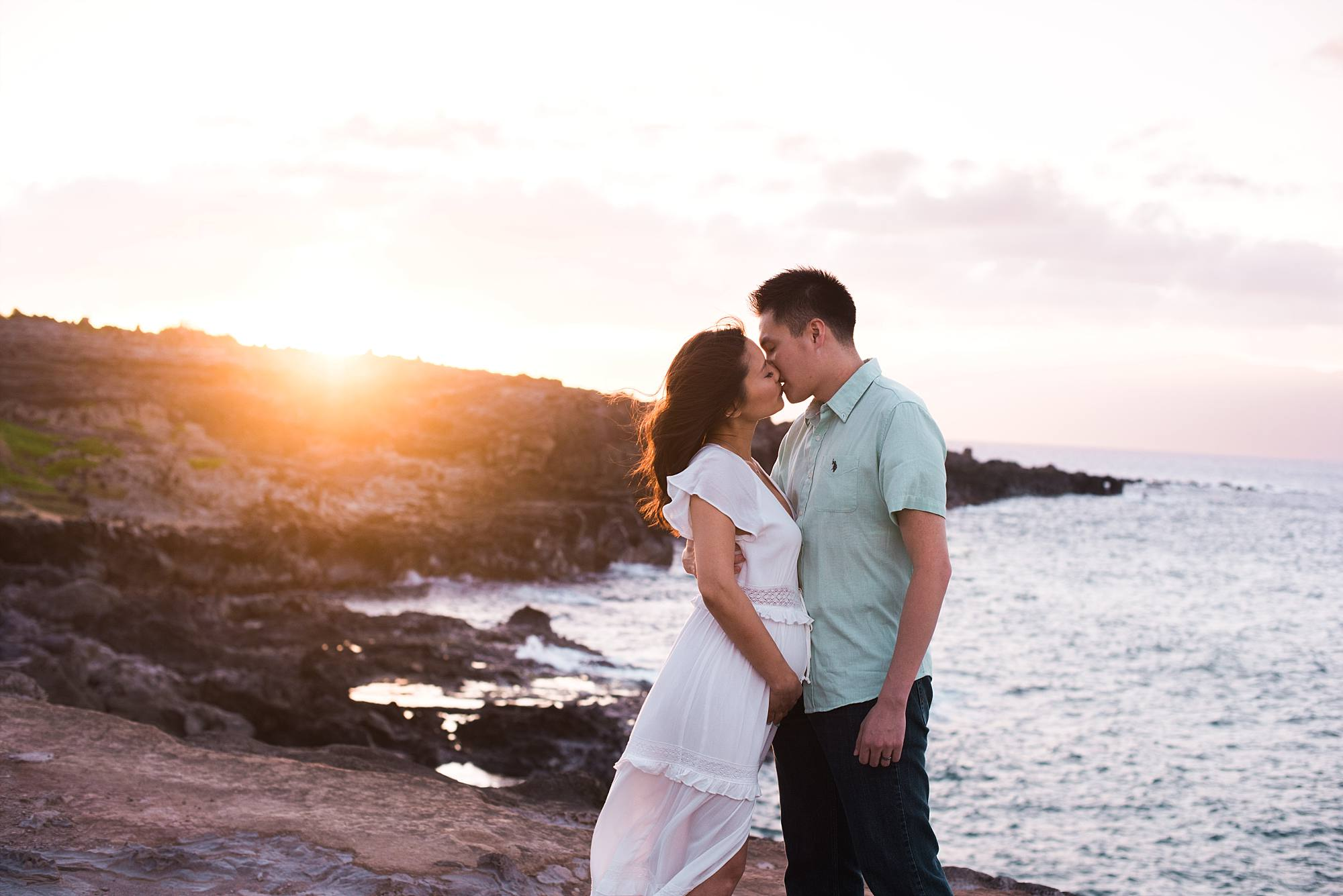 romantic shot of pregnant couple kissing on the cliffs of honolua