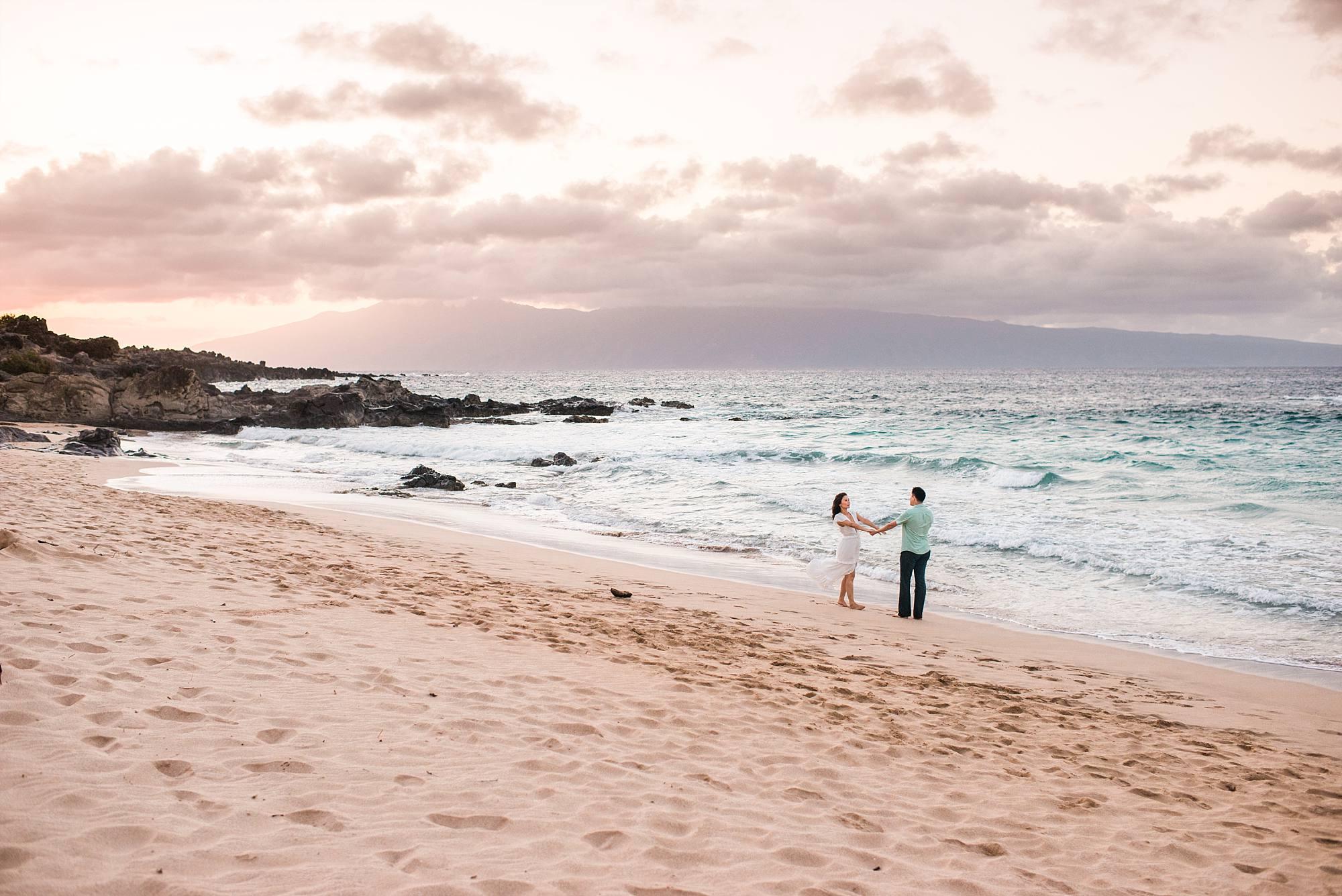 beach maternity shot of couple dancing on the beach