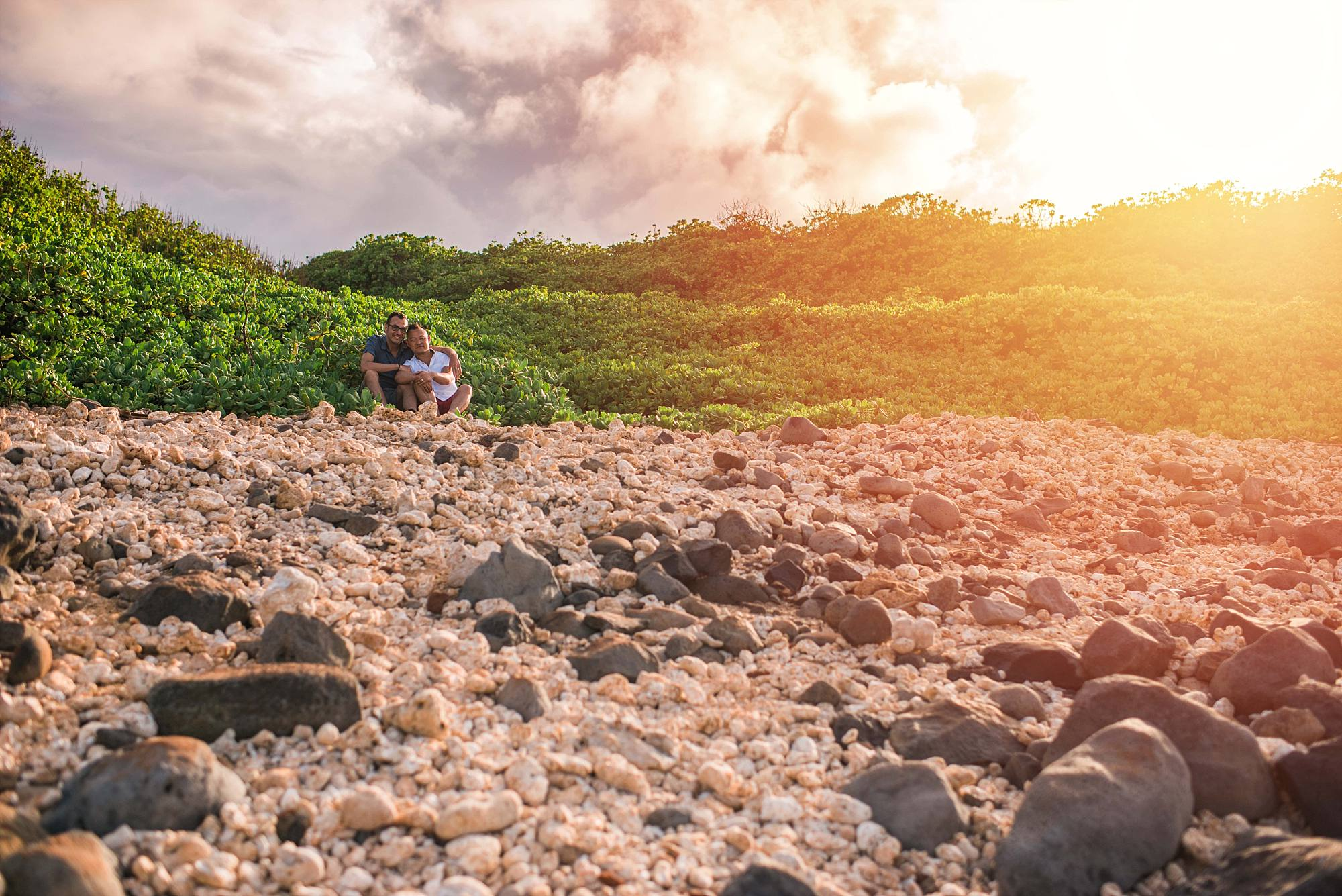 happy couple sitting in greenery with a sea of rocks in the foreground
