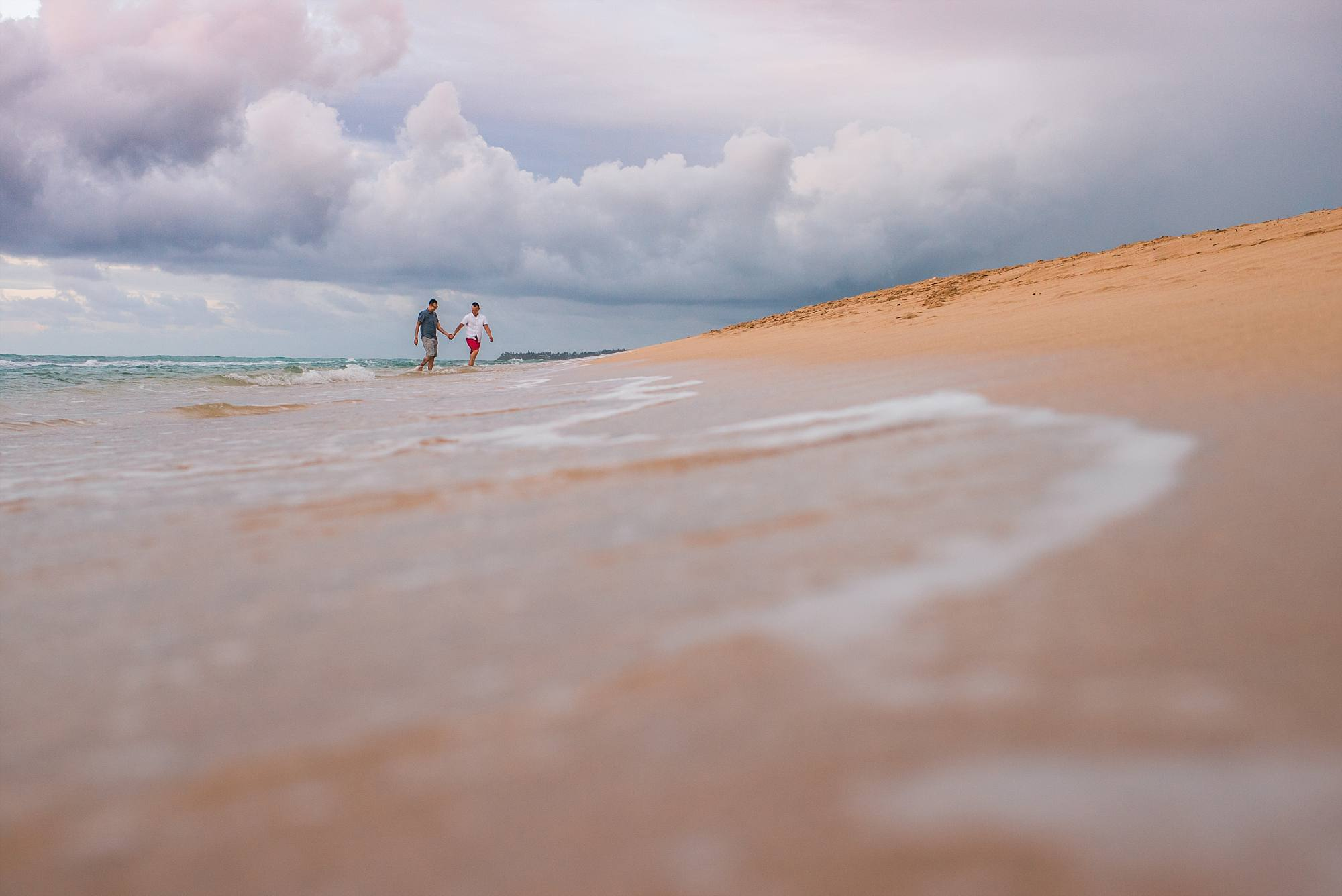 romantic shot of fiances walking through the waves and storm clouds in the distance