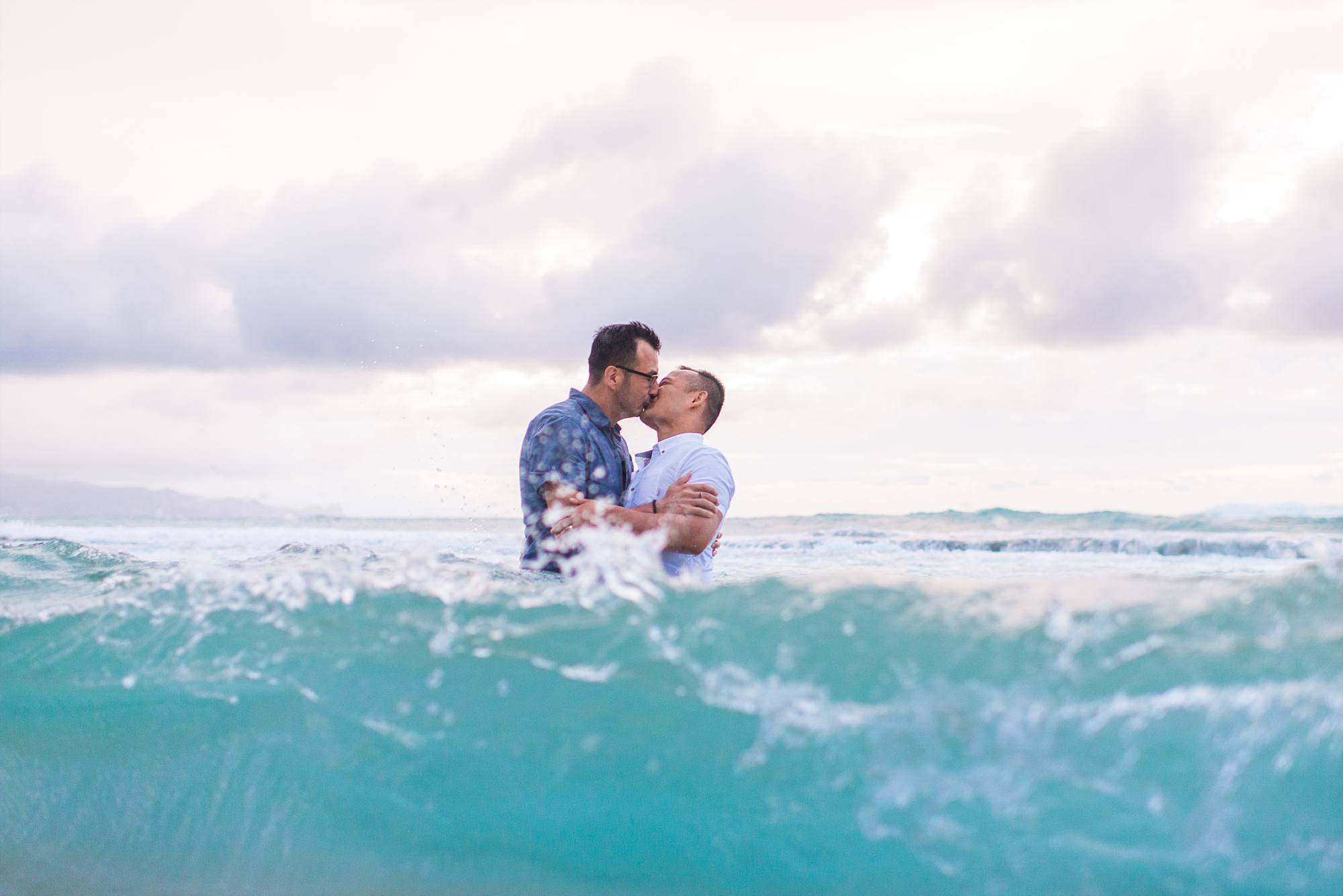 Fiances kissing while standing in the ocean and waves coming in