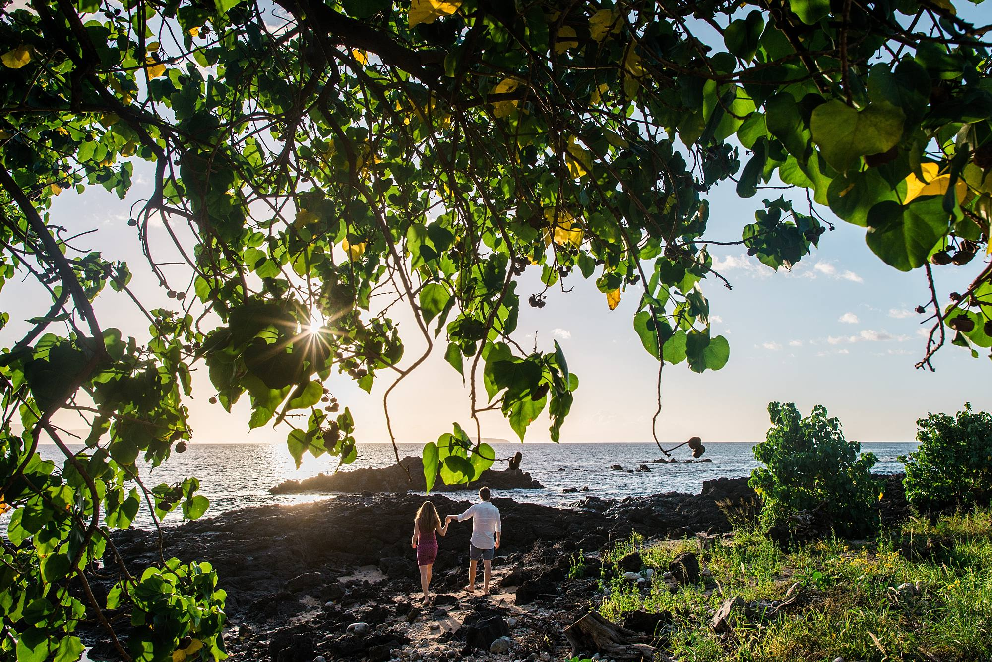 husband and wife on adventurous maternity shoot on Maui, traversing lava rocks to get just the right shot