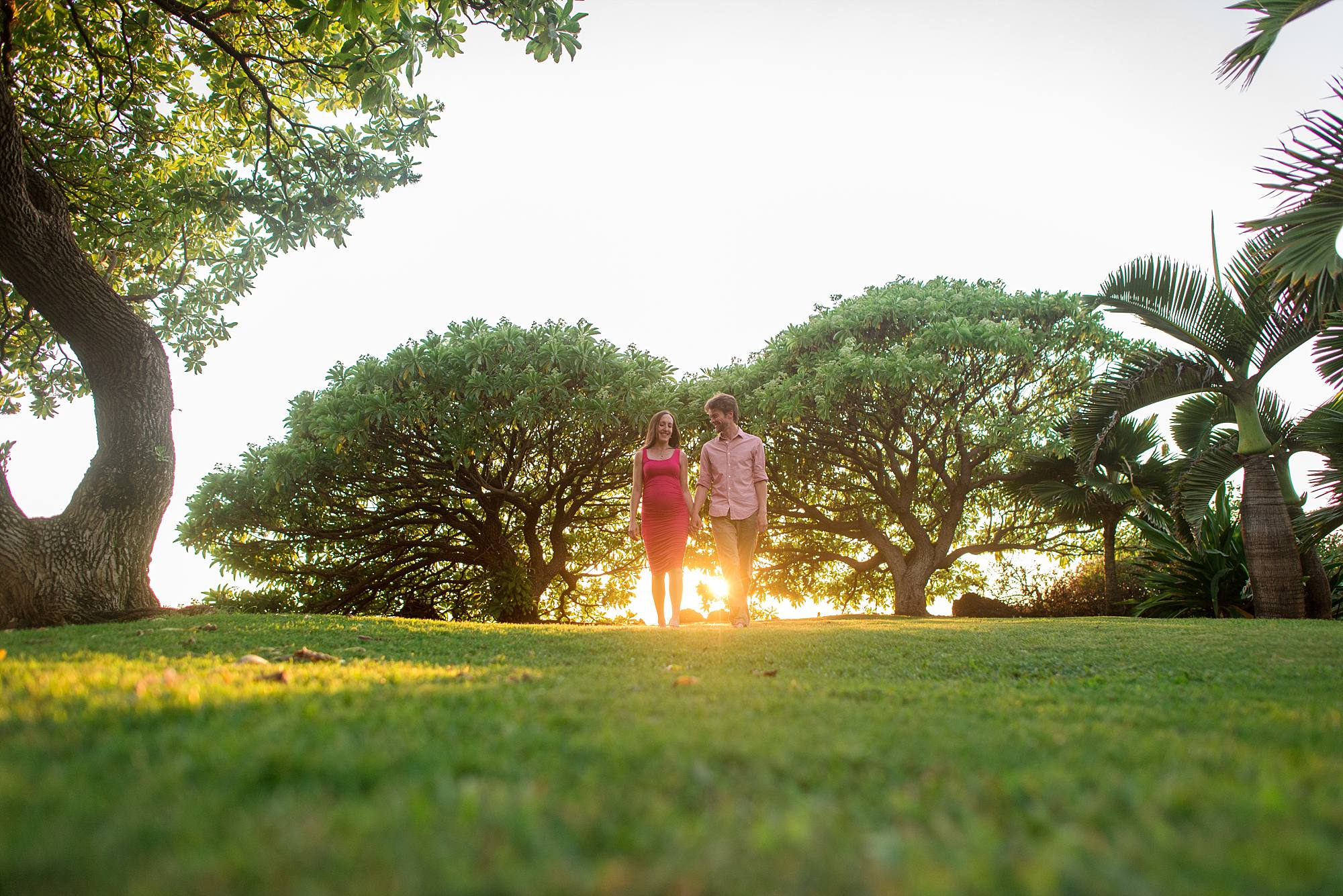 couple expecting baby walking through the grass with beautiful trees behind them and the golden light shining