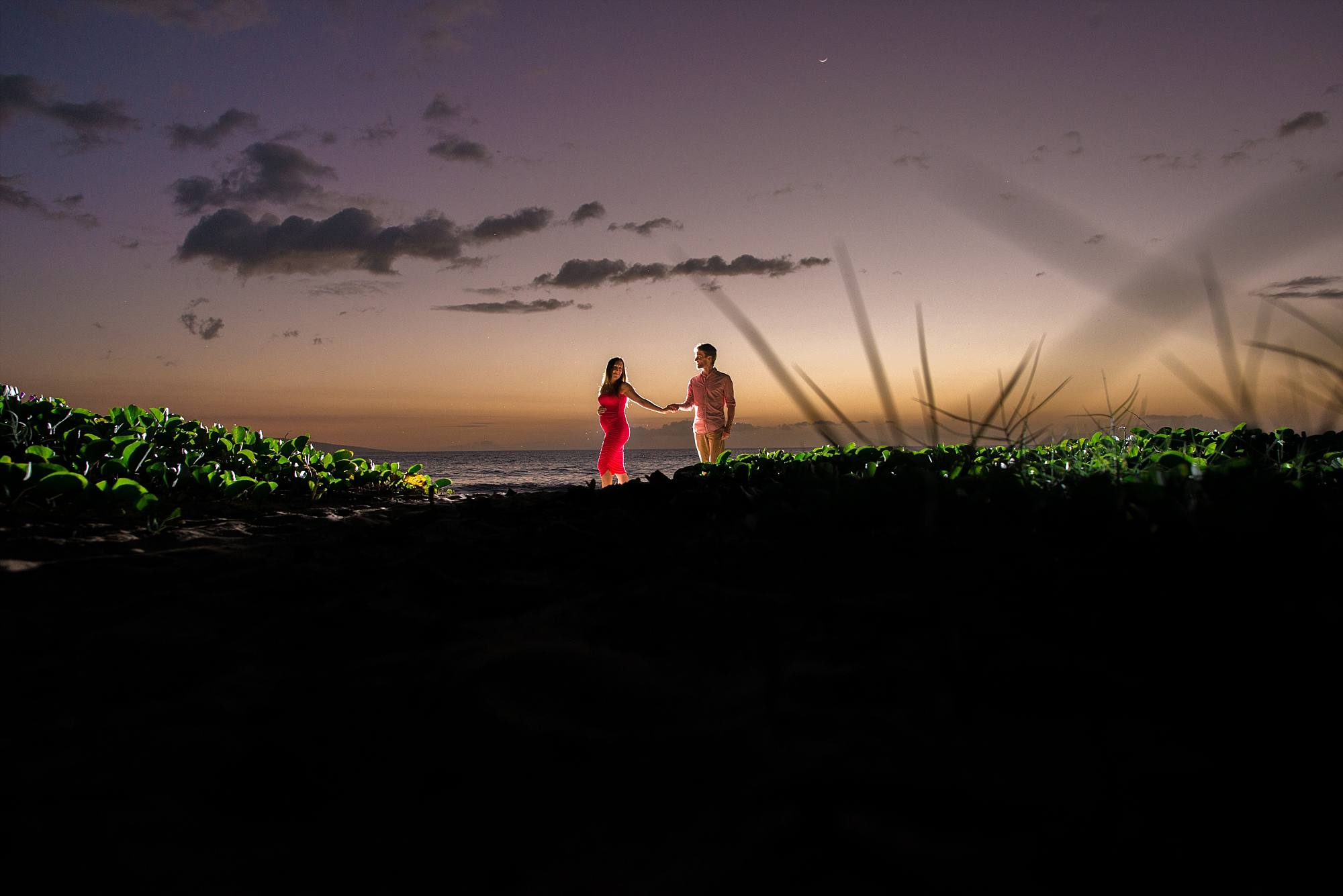 back lit sunset maternity shot on beach with Maui greenery popping in the foreground