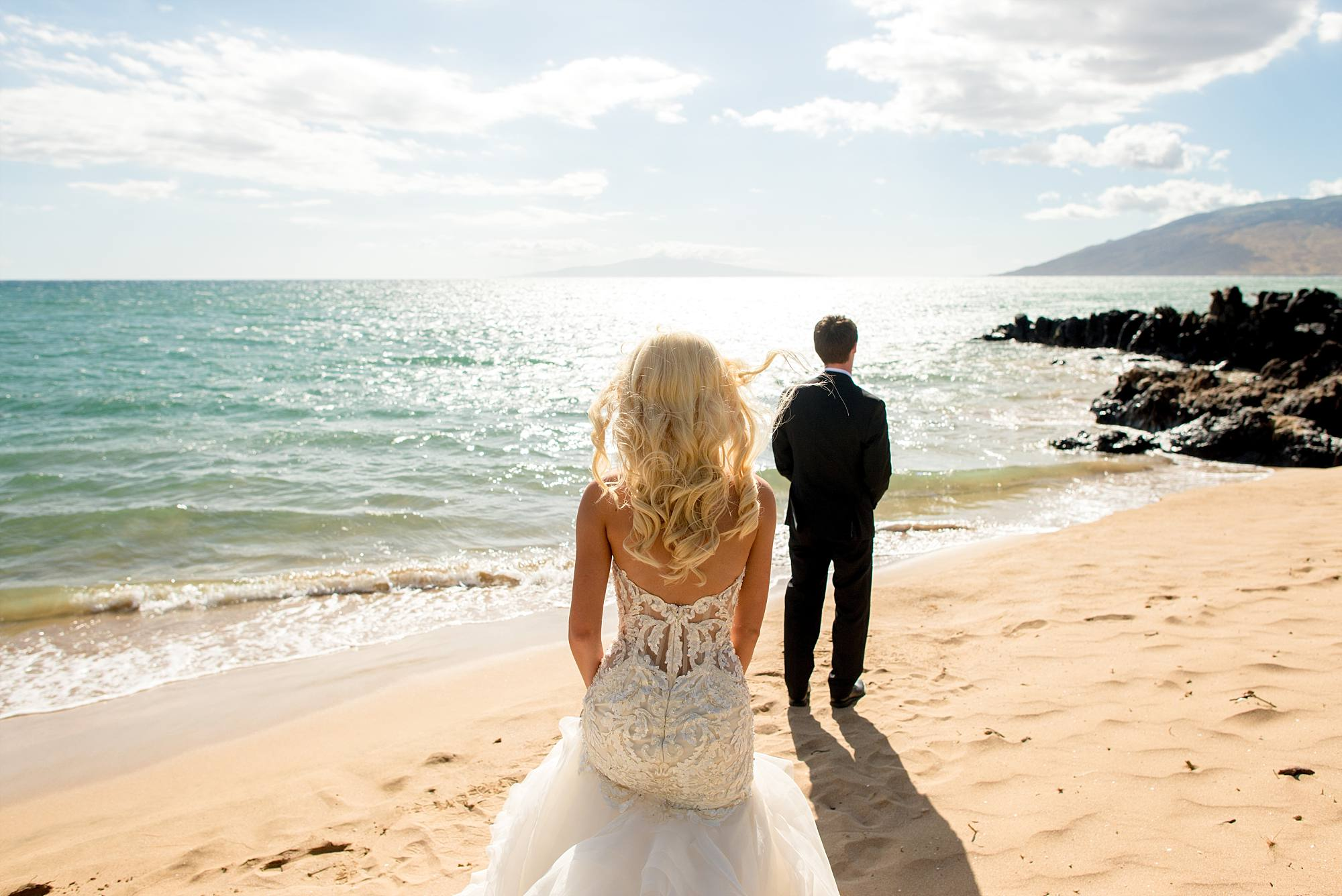 bride standing behind groom just before their first look on a sunny Kihei Maui beach
