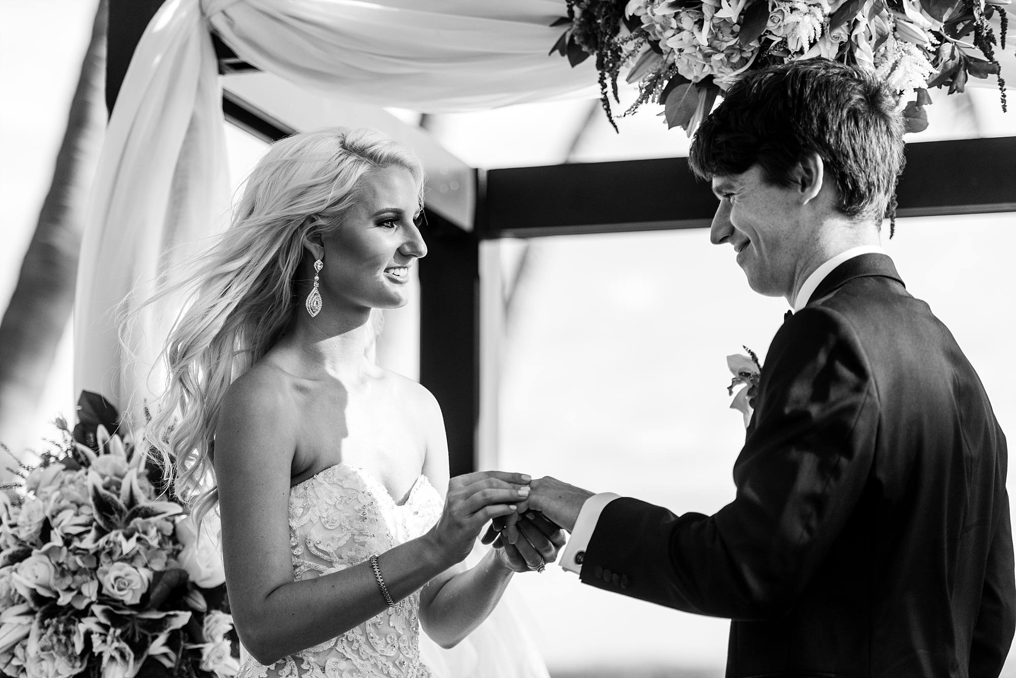 wedding couple exchanging rings, wind in their hair