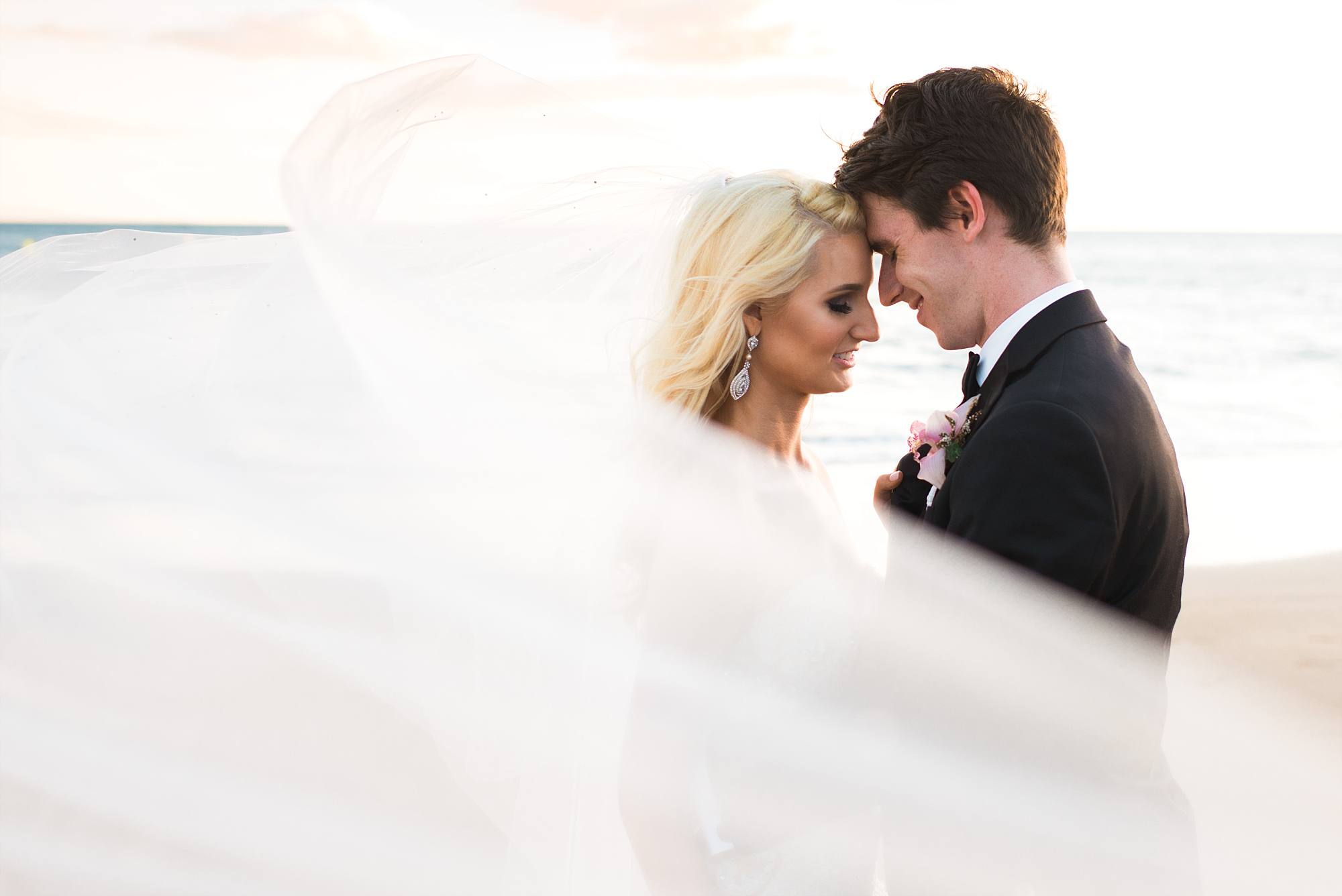 bride and groom standing head to head with veil swooping around them