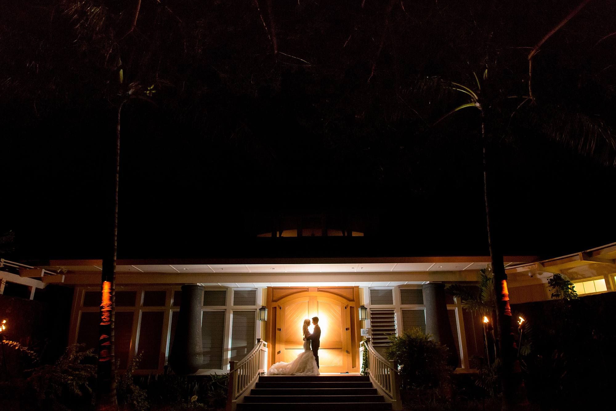 back lit night time photo of wedding couple on steps of beach house at Sugar Beach Events Wedding