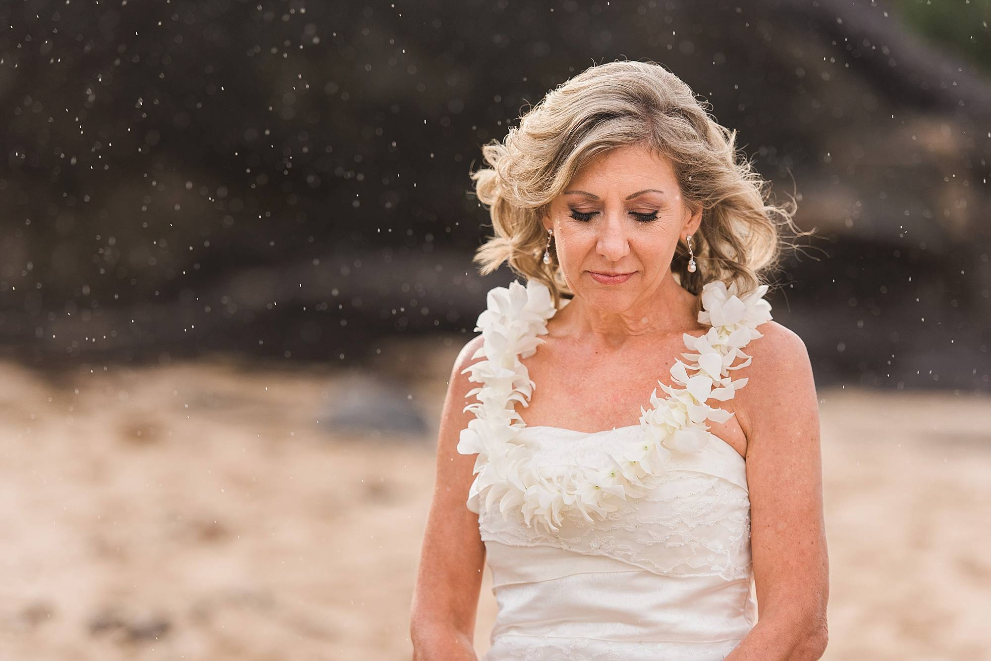bride praying in the rain in Maui