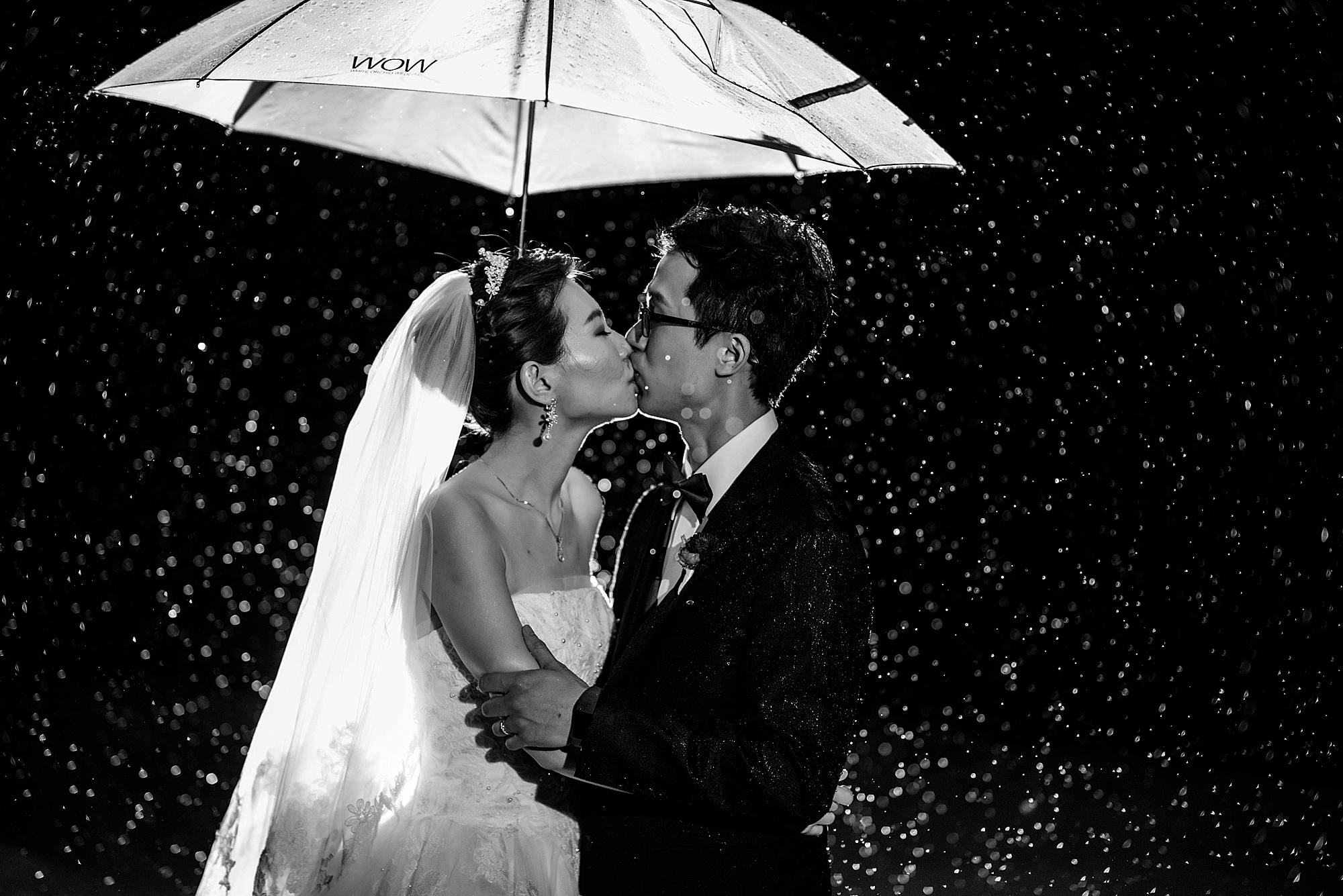 photo of a couple kissing in the rain at white orchid beach house maui