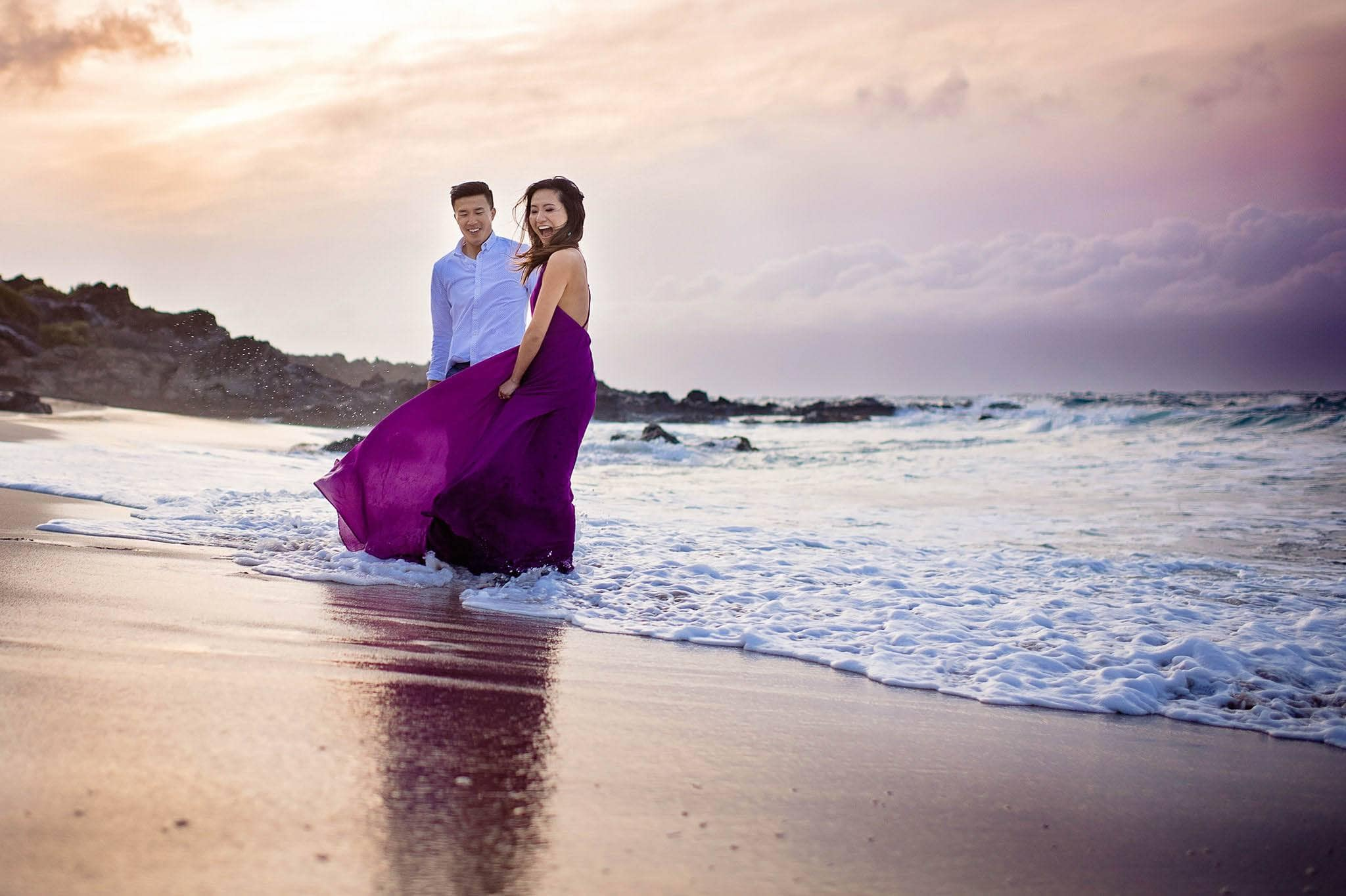 engaged couple playing in the ocean in maui