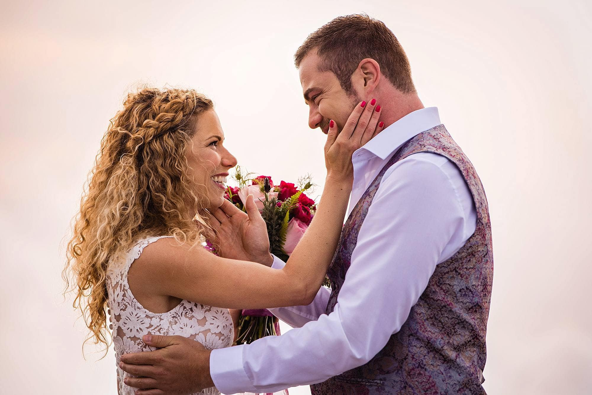 bride and groom touching each other's faces during ceremony