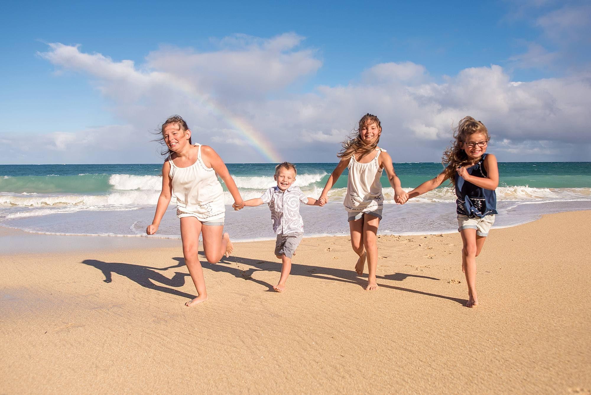 kids running on beach with rainbow
