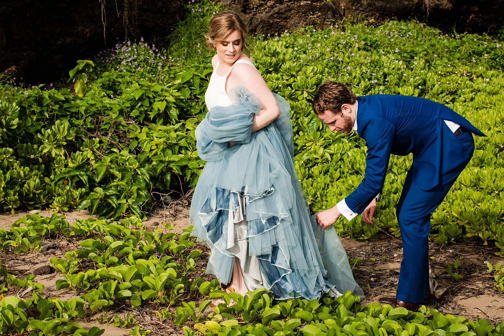 groom getting sticks out of bride's dress