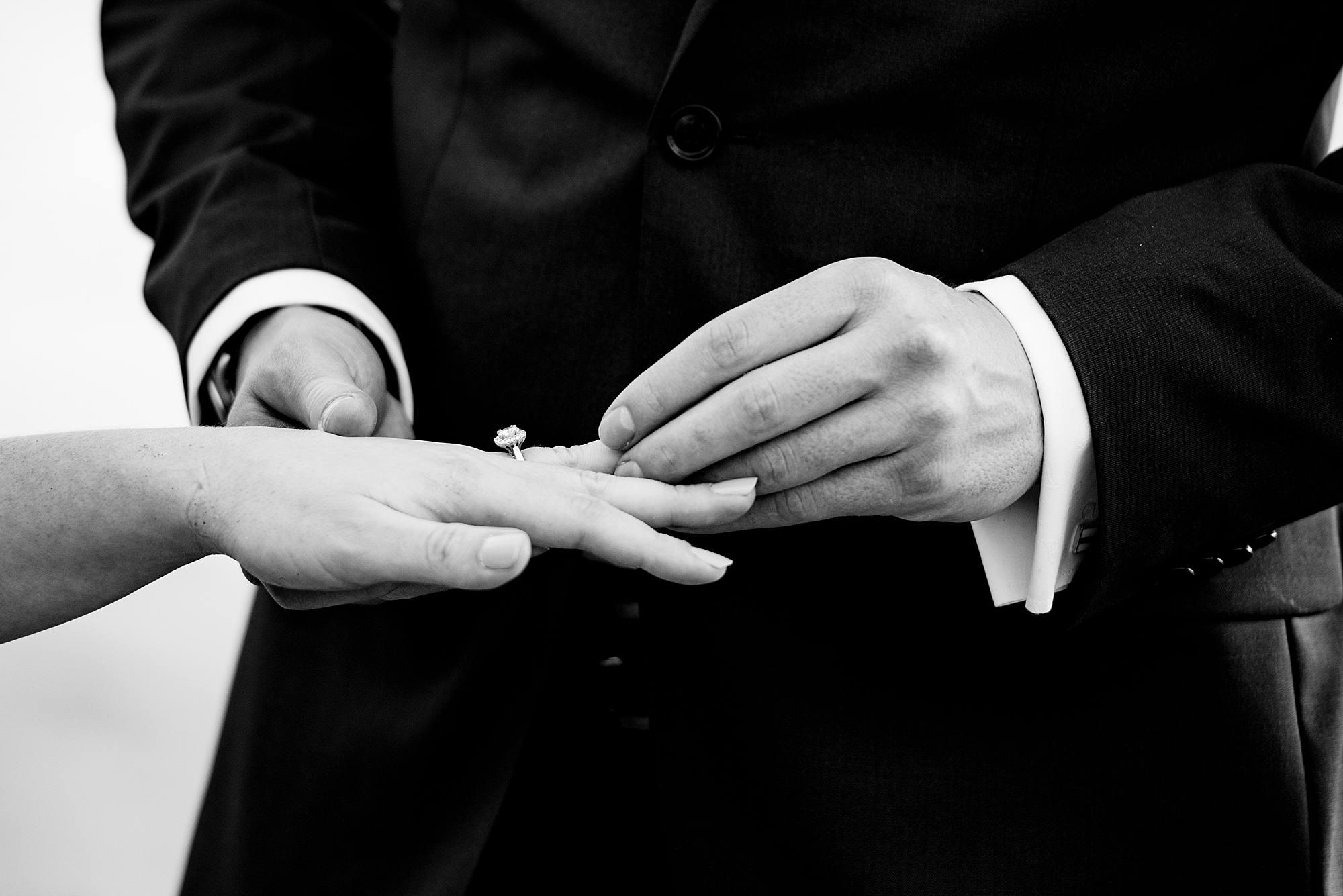 groom putting ring on bride