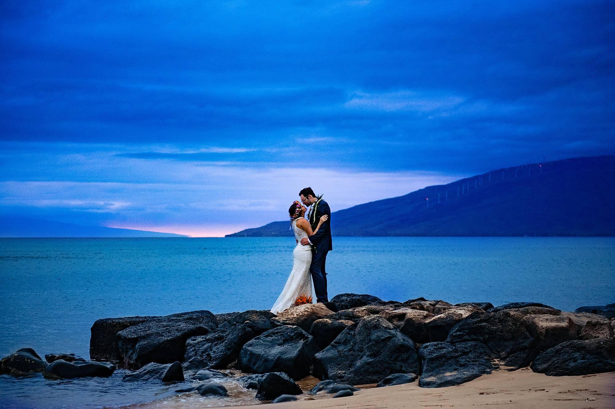 bride and groom kissing on rocks