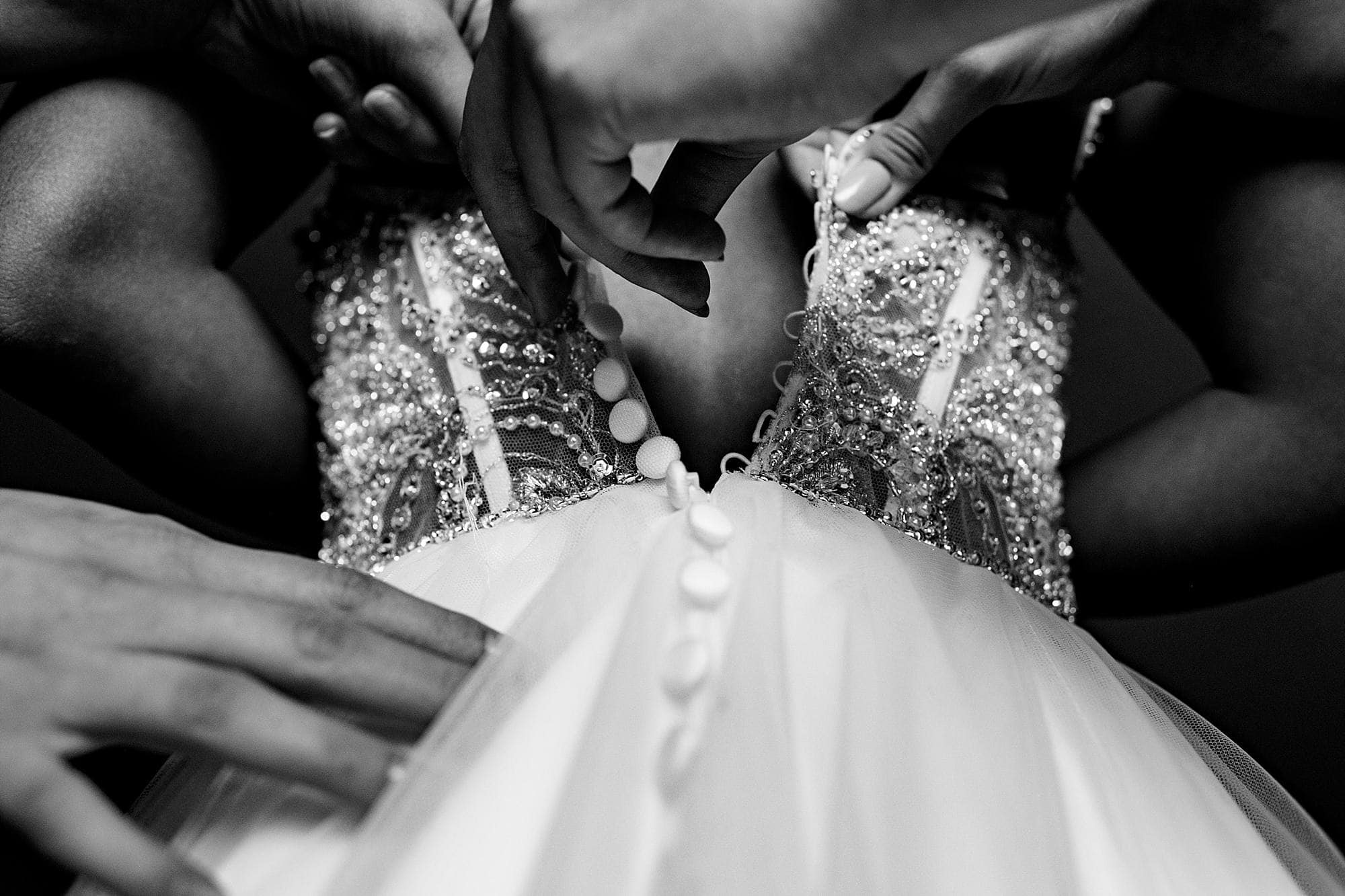 bridesmaids buttoning bride's dress