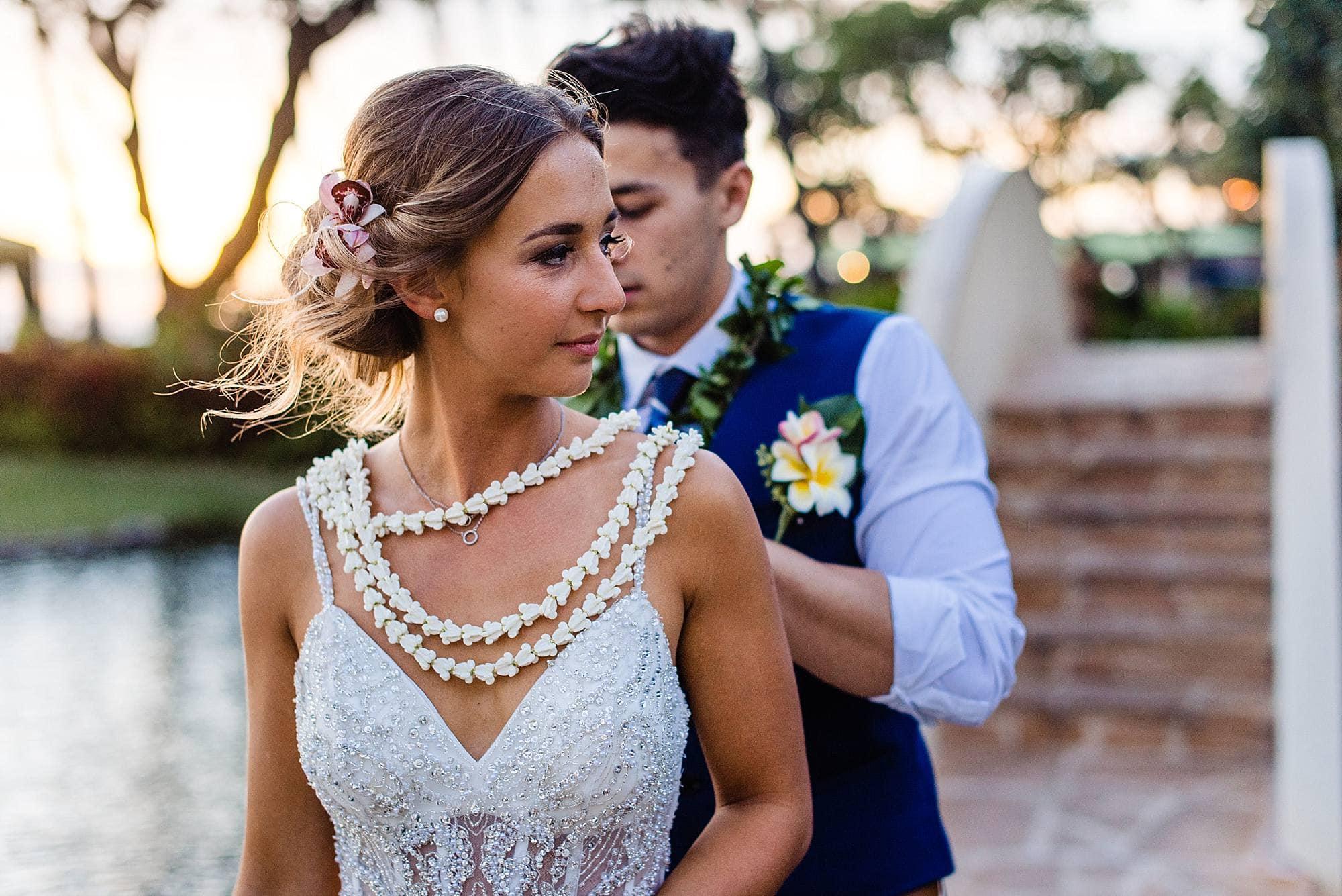 groom fixing bride's leis