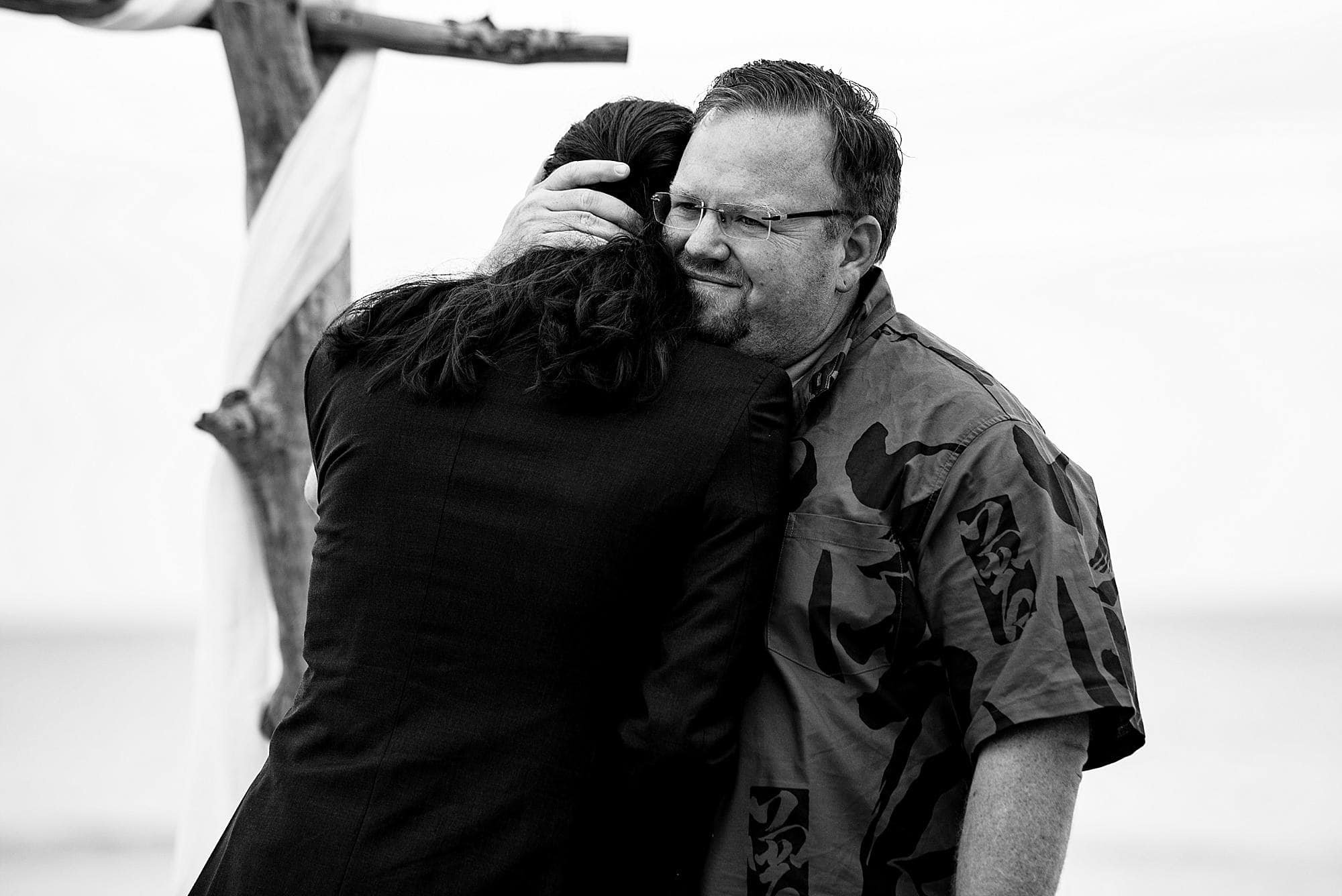 groom and officiant hugging