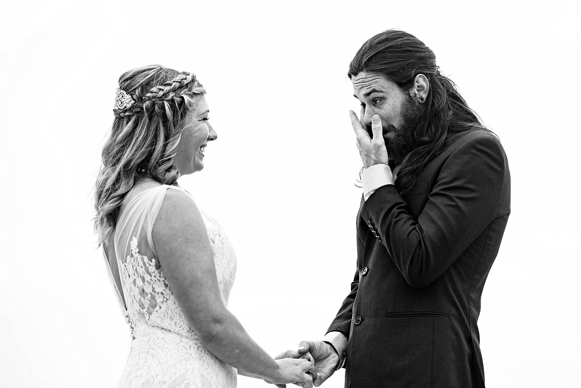 groom wiping tears during wedding