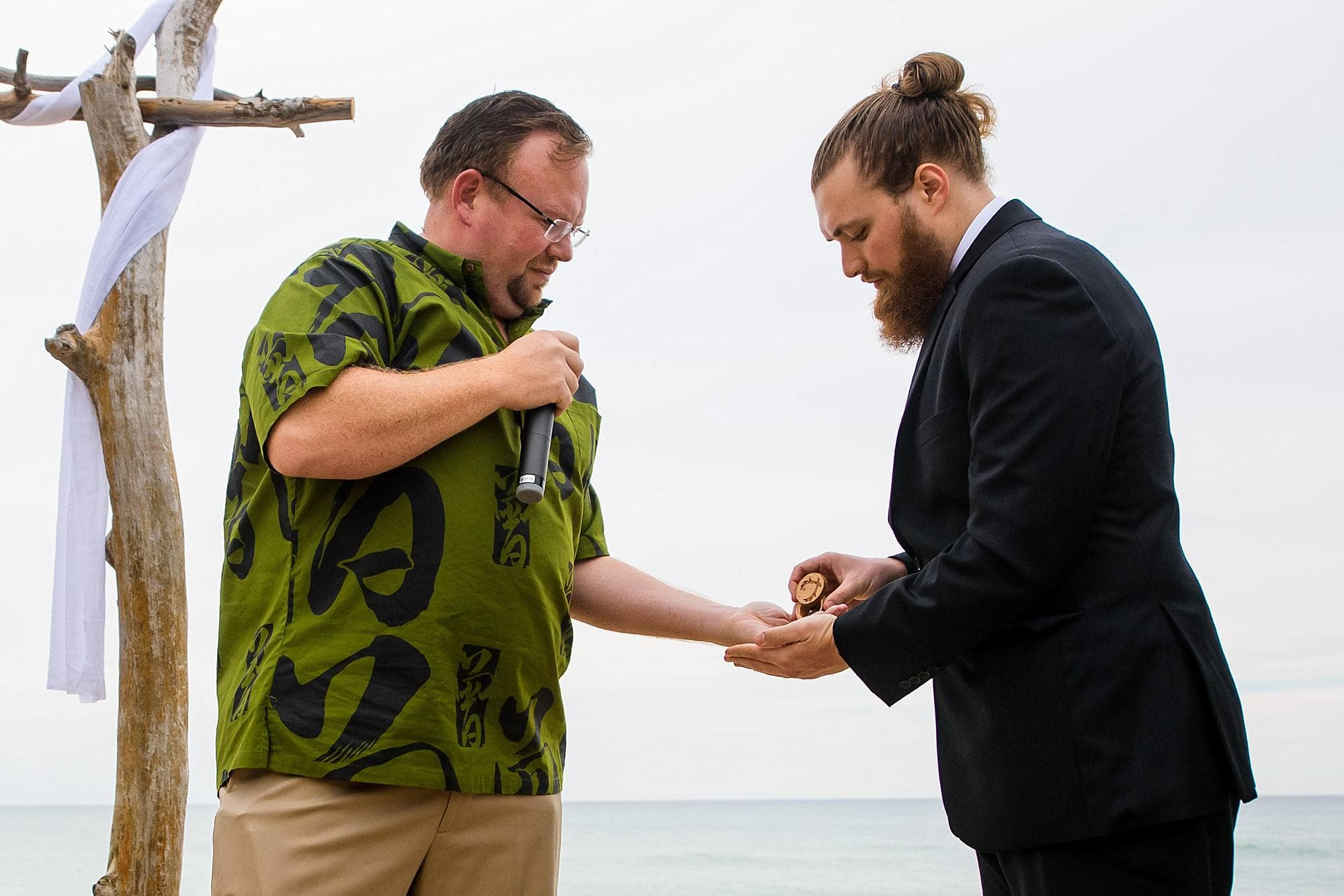 best man giving rings to officiant