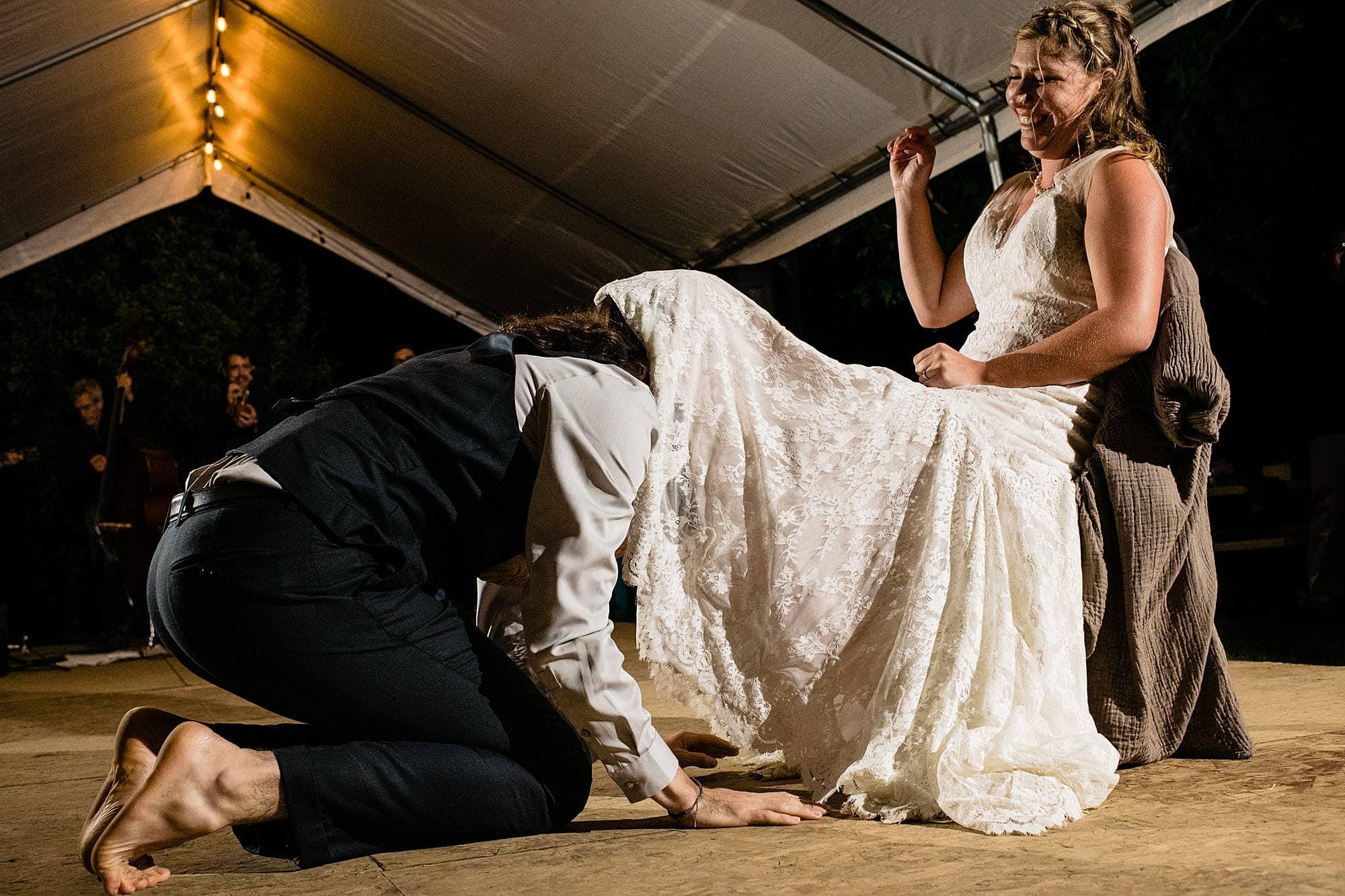 groom retrieves garter at west michigan wedding reception