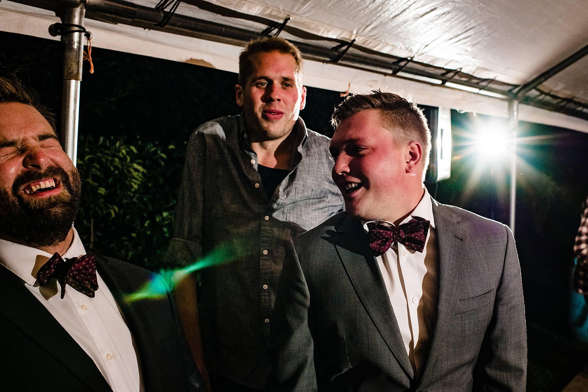 groomsment laugh at wedding reception at lemon creek winery
