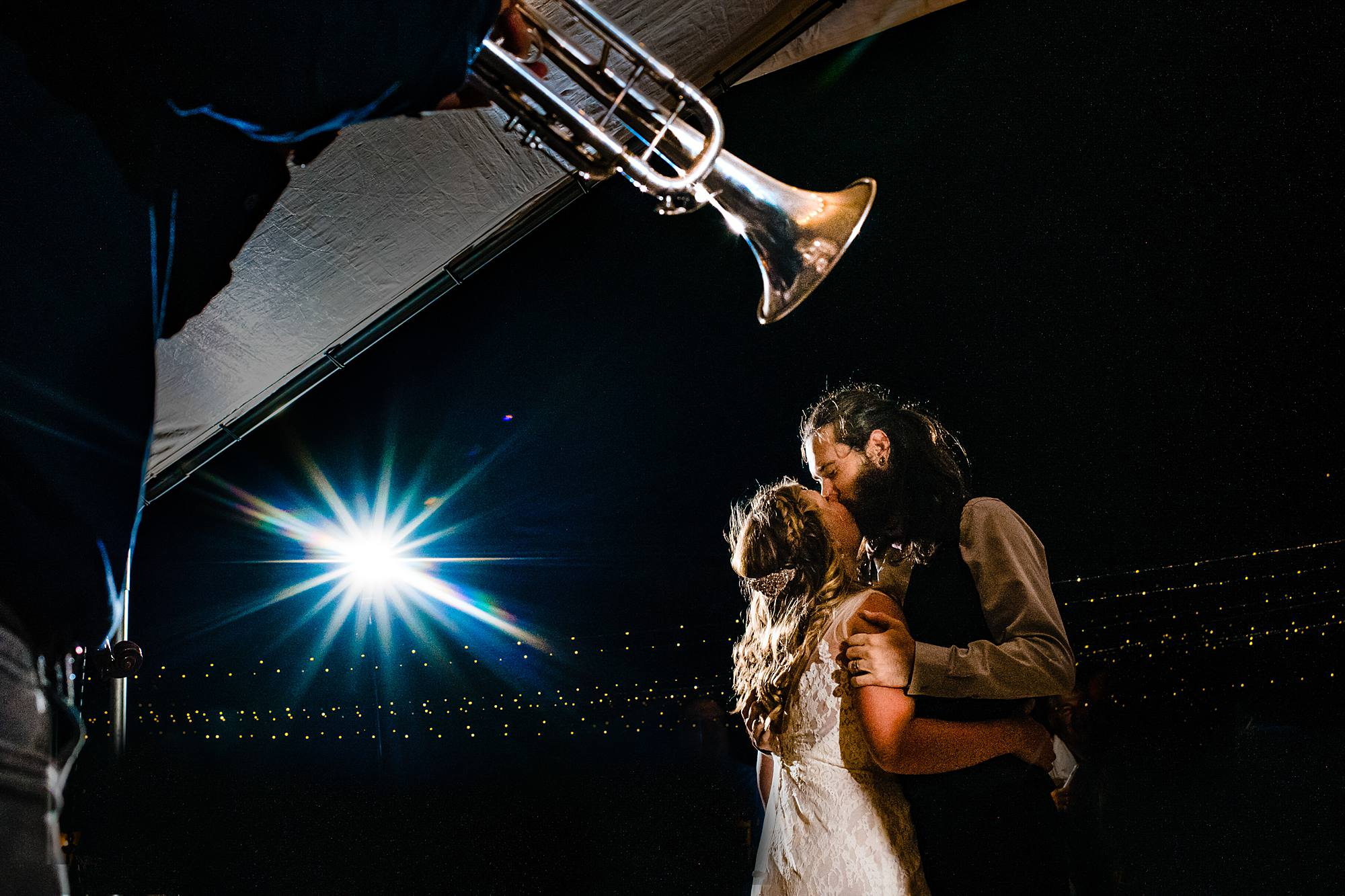 couple kissing at wedding reception with trumpet