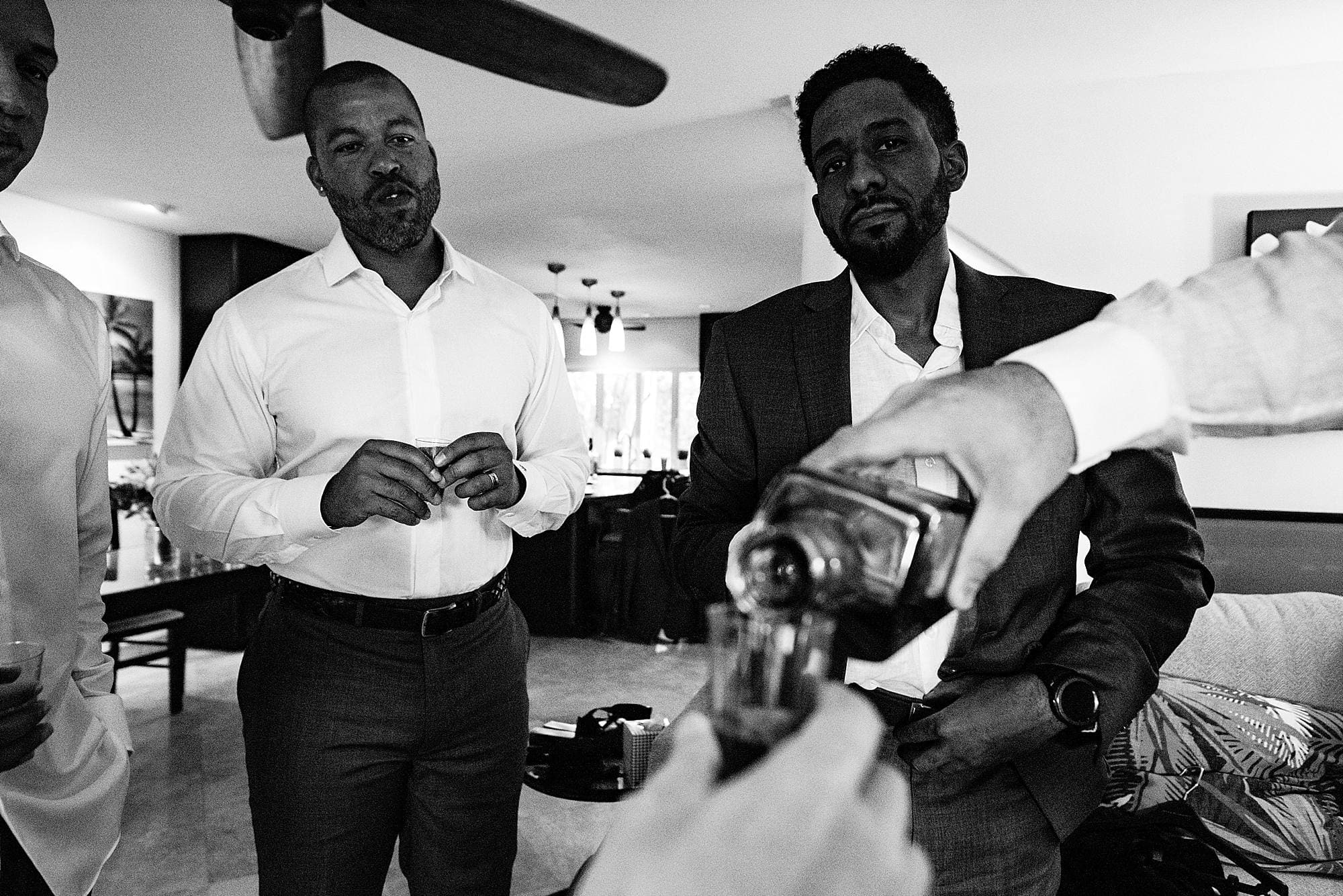 groom pouring shots of scotch before wedding