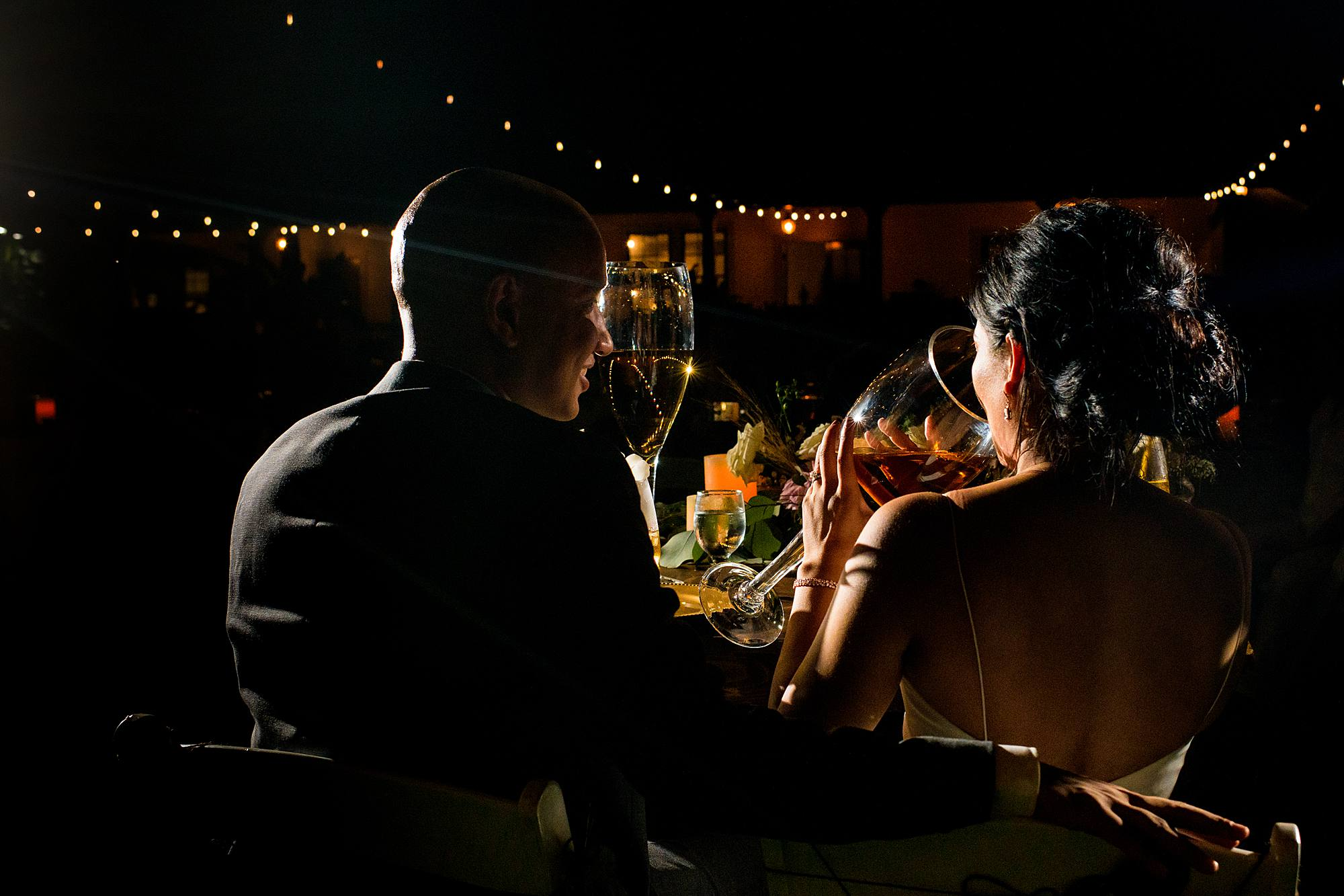 bride and groom drinking from large wine glasses