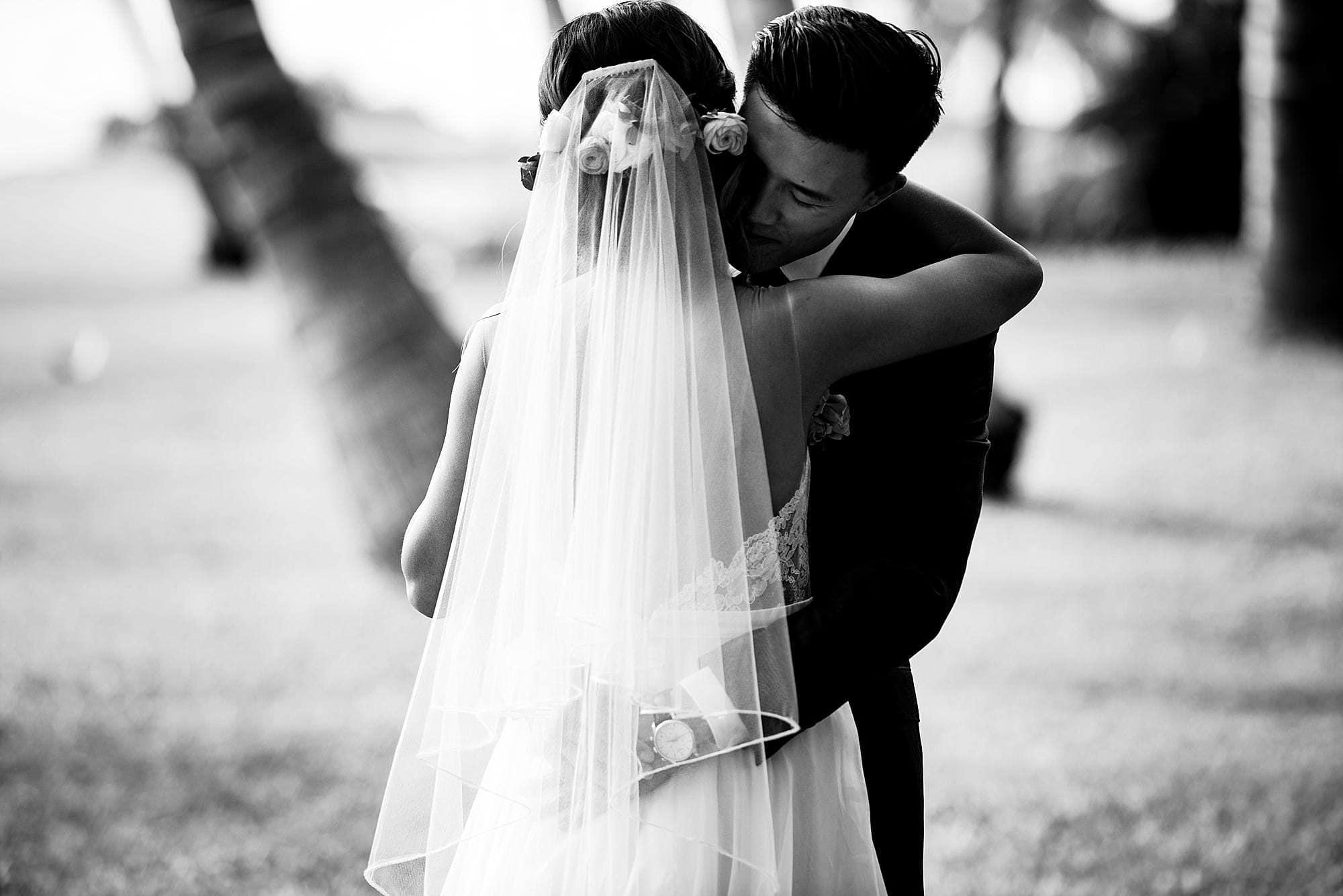 black and white image of groom hugging bride