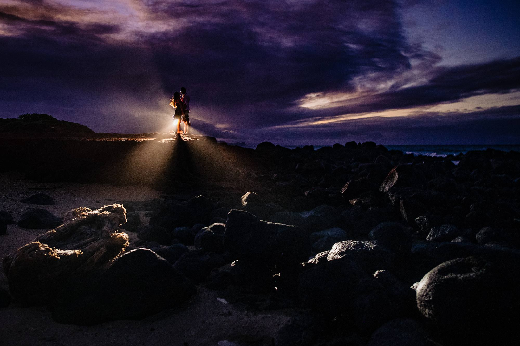 couple on a cliff in maui with epic lighting