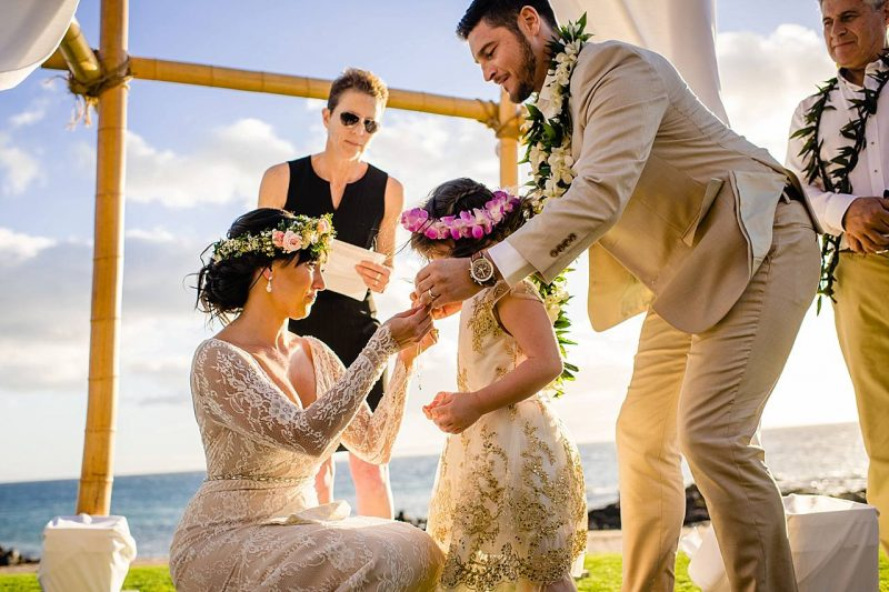 bride and groom presenting daughter with necklace