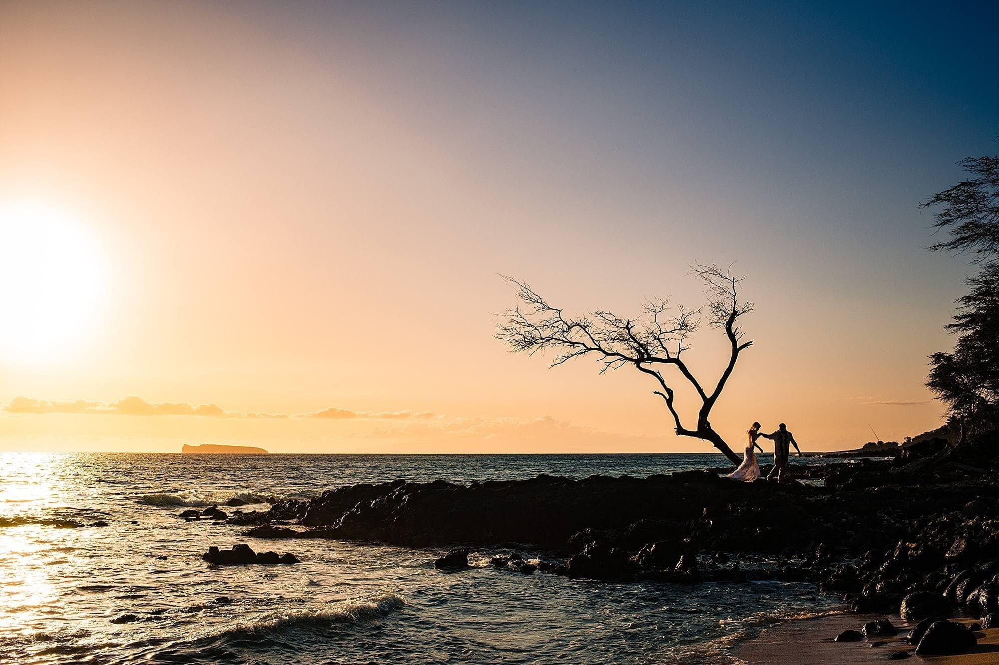 silhouette of bride and groom on lava rocks in hawaii