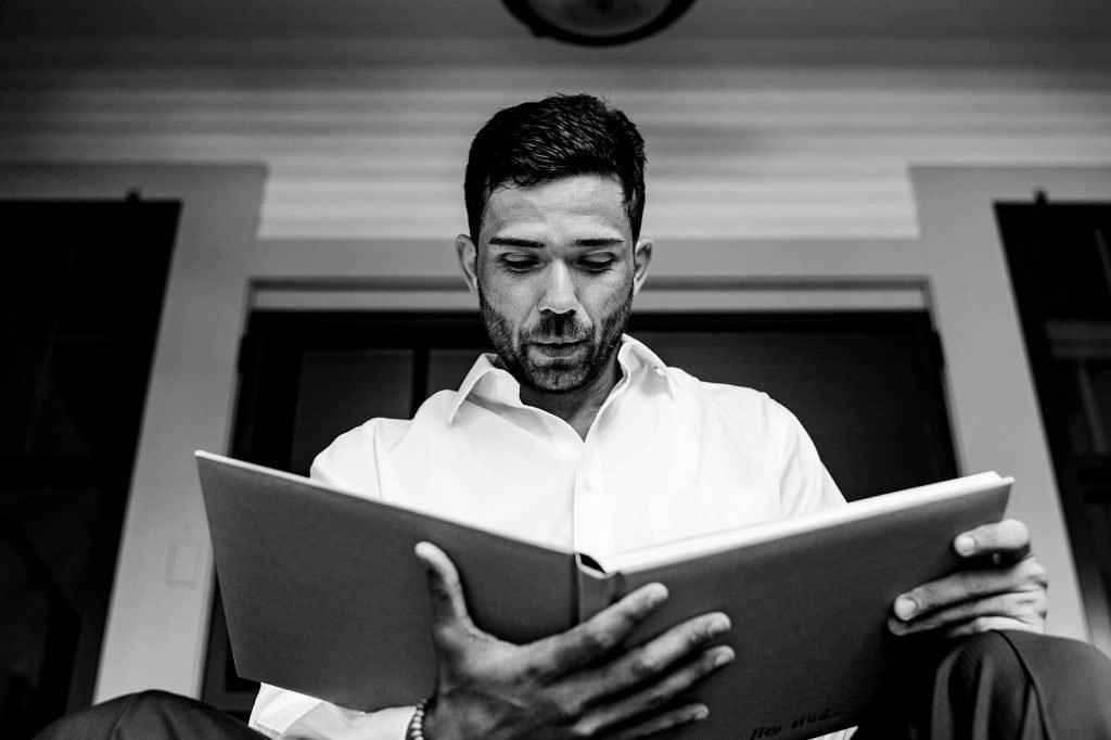 groom looking at boudoir book